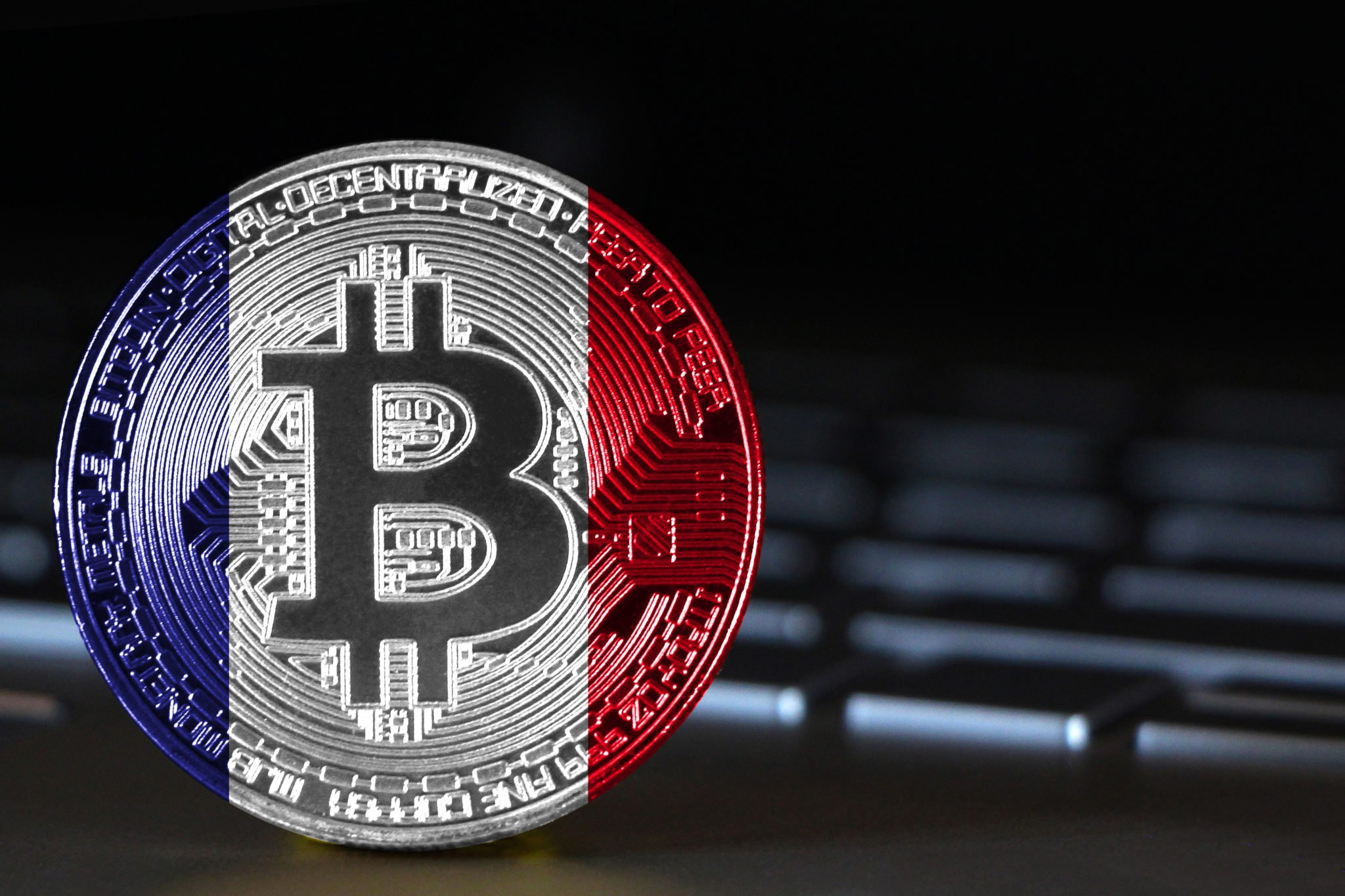Bitcoin close-up on keyboard background, the flag of France is shown on bitcoin.