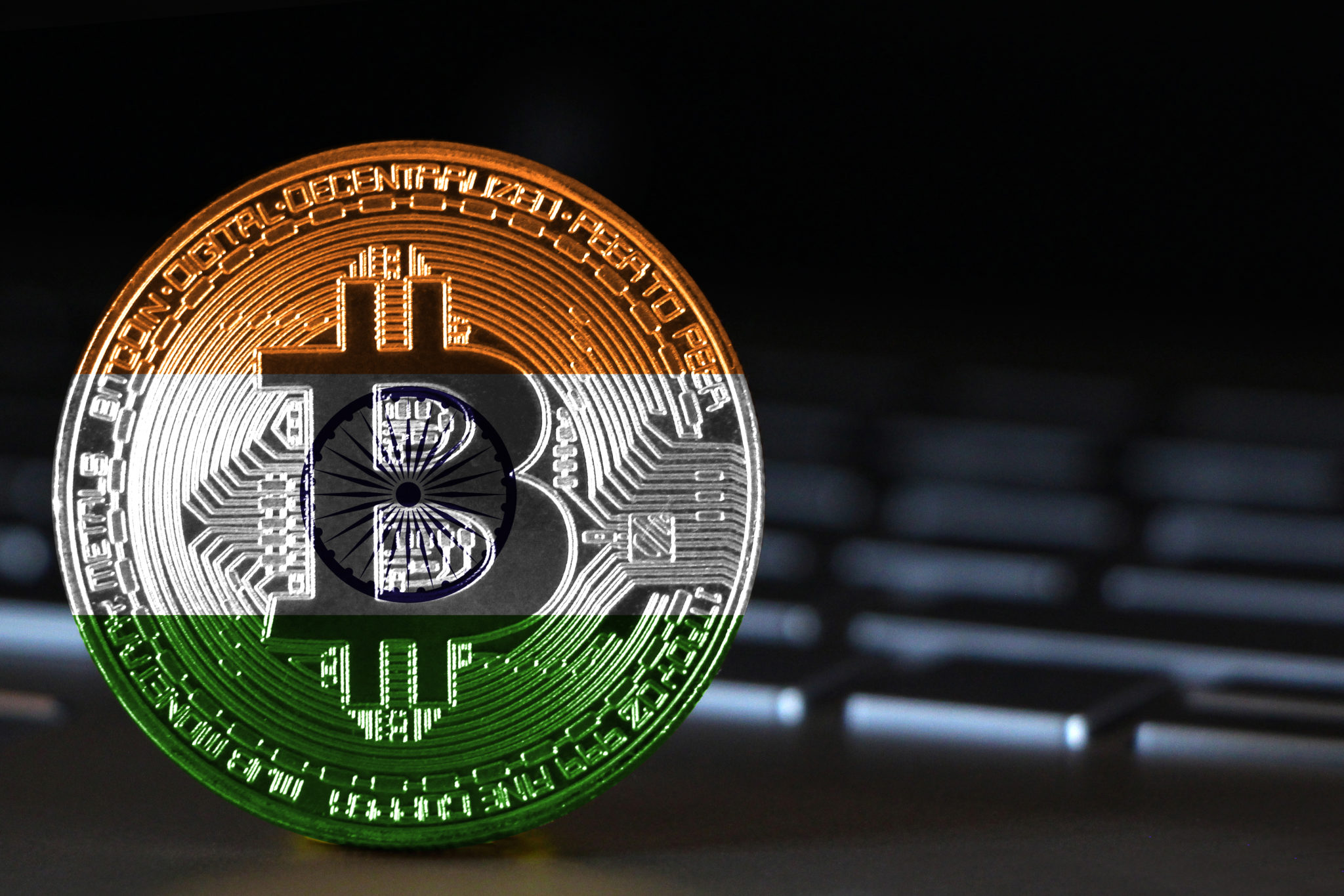 Bitcoin close-up on keyboard background, the flag of India is shown on bitcoin.