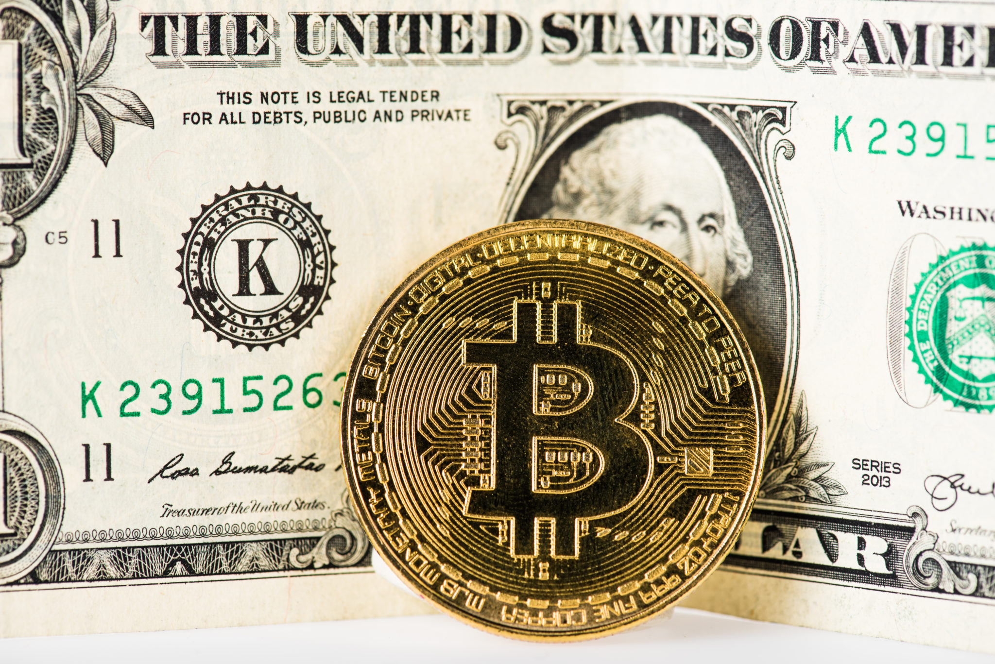 close-up view of bitcoin and dollar banknote on white