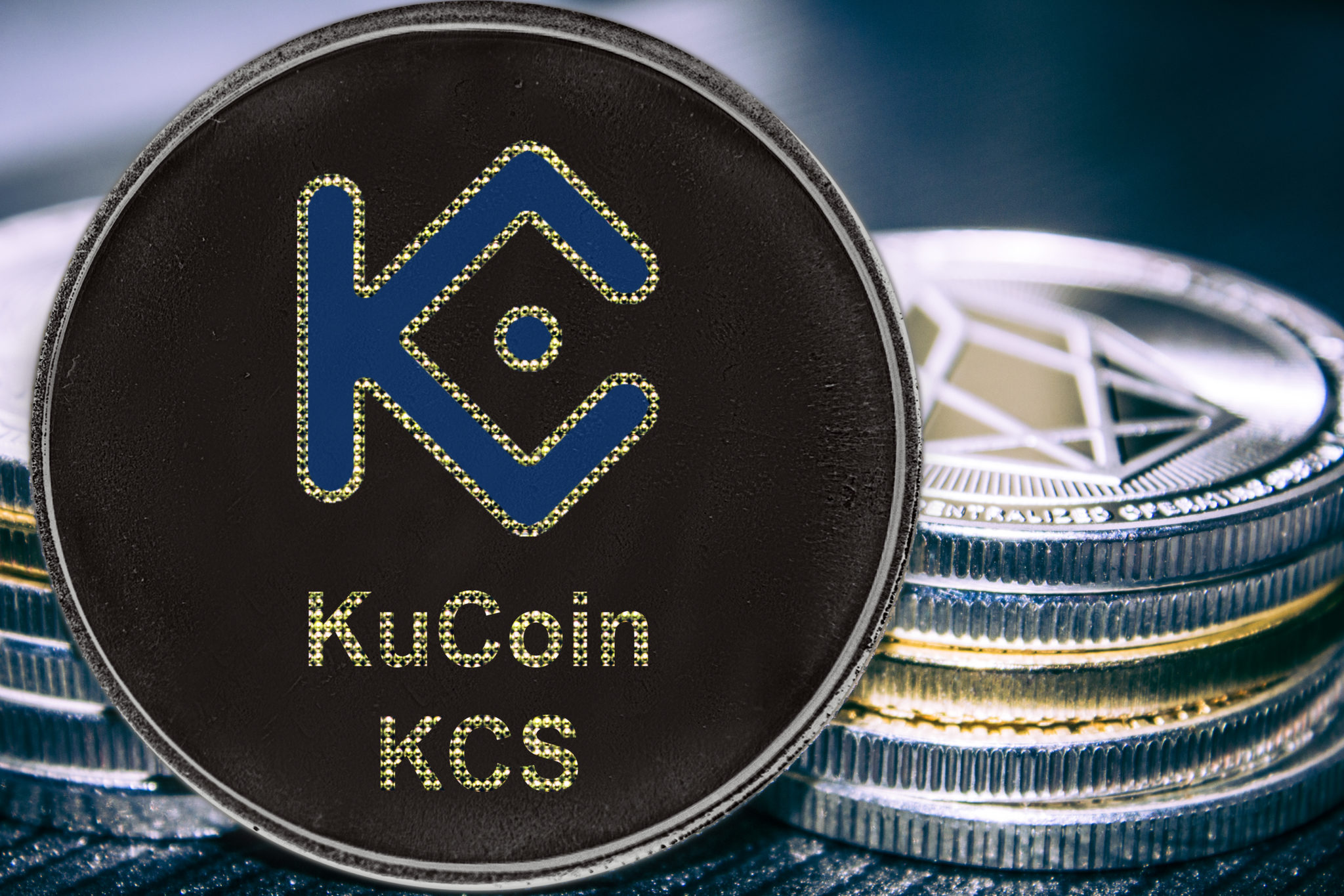 Coin cryptocurrency KuCoin KCS on the background of a stack of coins.