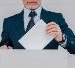 cropped view of bearded businessman voting near brick wall