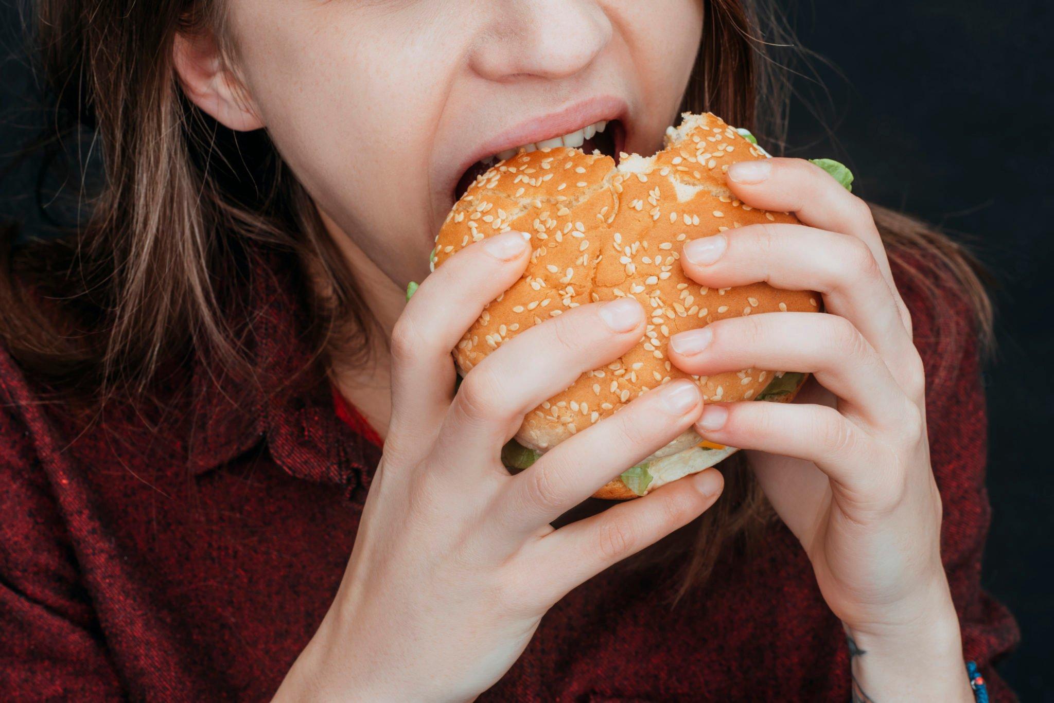cropped view of girl biting tasty hamburger
