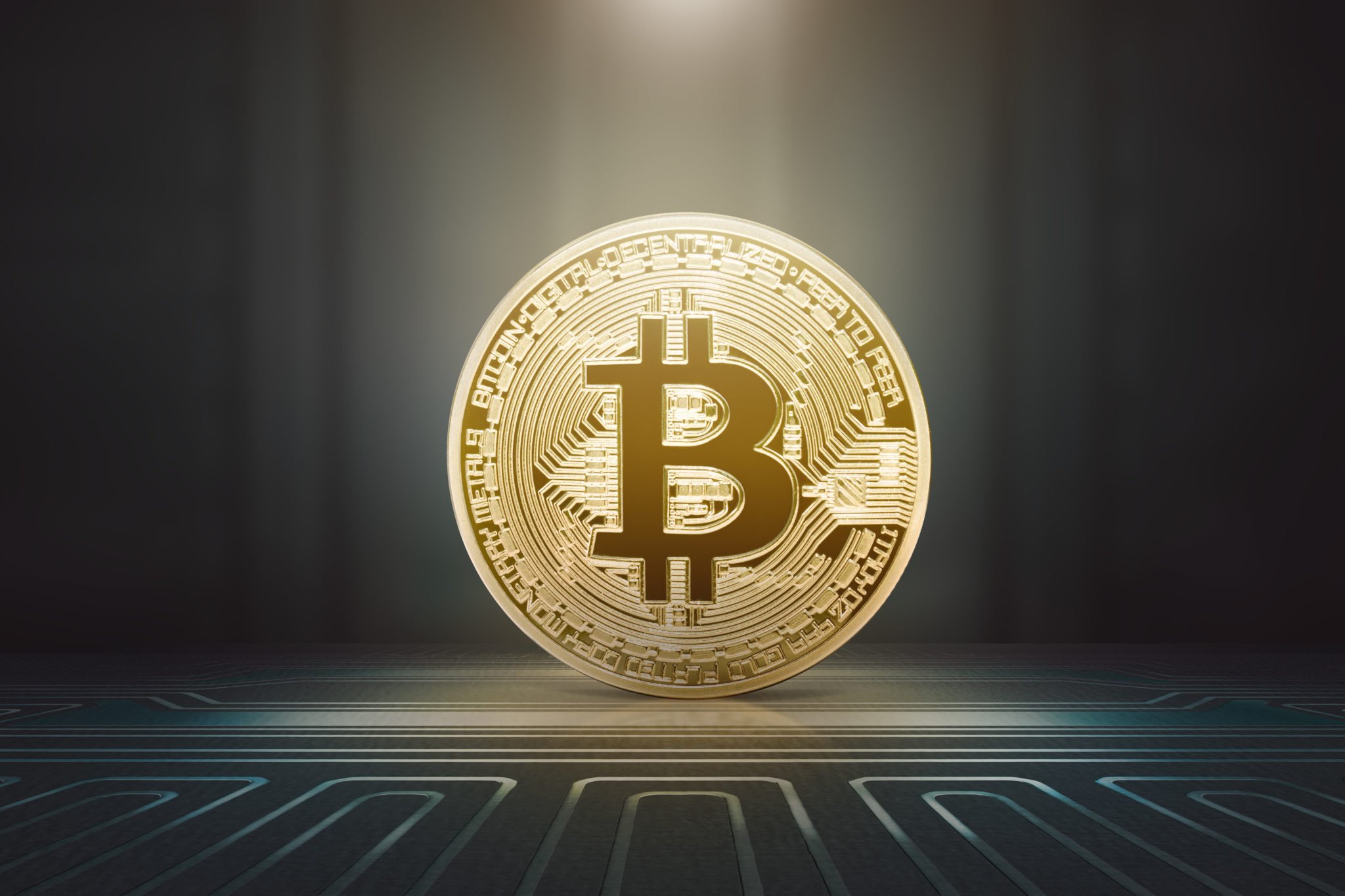 Golden bitcoin on electrical circuit with bright background