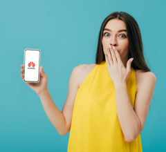 KYIV, UKRAINE - JUNE 6, 2019: shocked beautiful girl in yellow dress showing smartphone with huawei logo isolated on turquoise