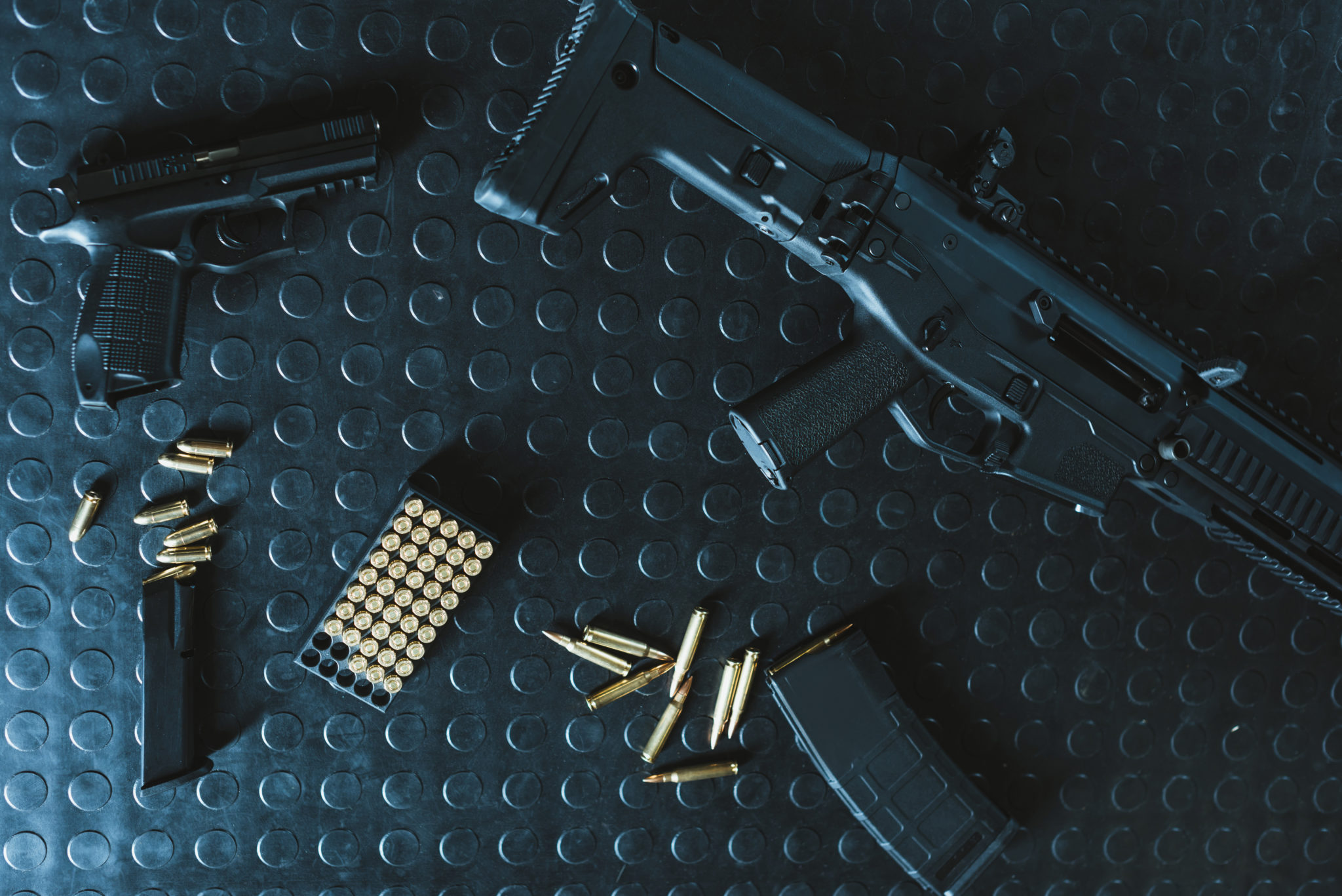 top view of gun and rifle with bullets on table