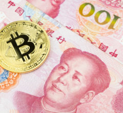 Golden bitcoin on pile of one hundred Chinese yuan banknotes background. Cryptocurrency, digital currency with yuan money bills.
