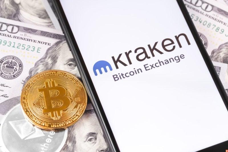 Bitcoin, dollars and Kraken logo of exchange on the screen