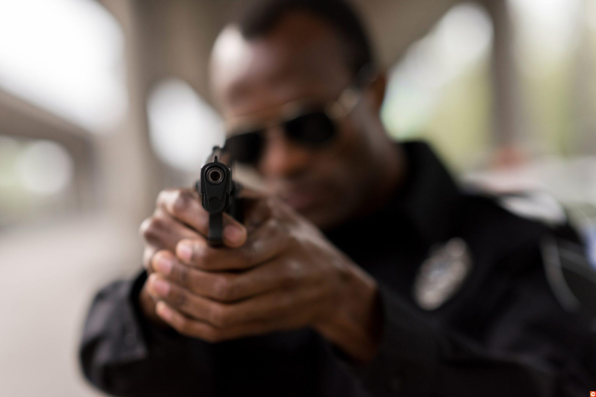 closeup shot of handgun in hands of african american policeman