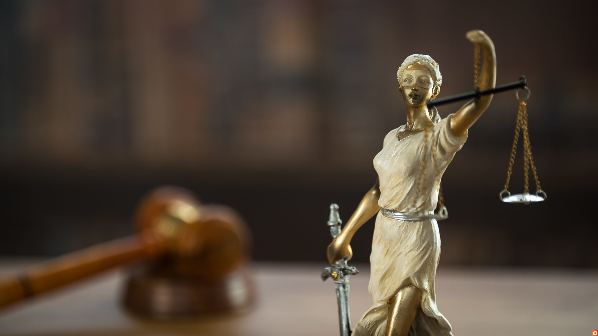 Law and Justice symbols on wooden table with blurred books background.