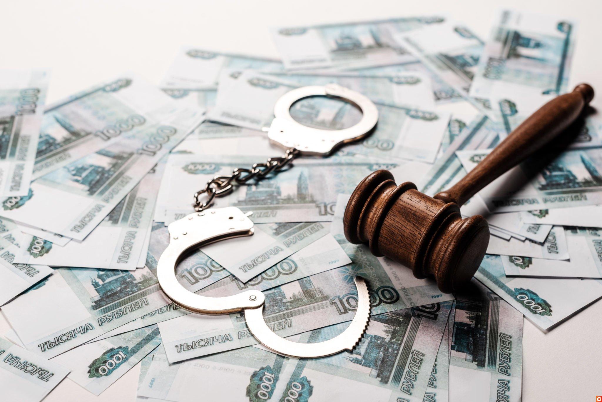 selective focus of gavel near metallic handcuffs on russian money