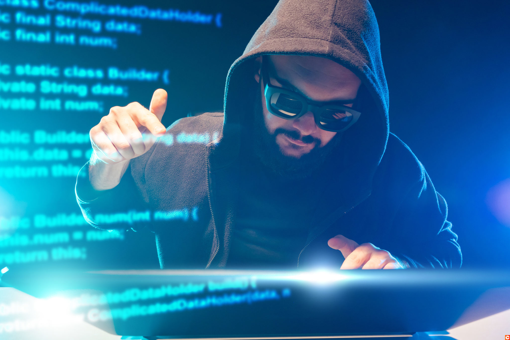 The concept of cybercrime. A man in black clothes and black glasses at the computer. Hacker on the background of an abstract fragment of computer code. Hacking computer programs.