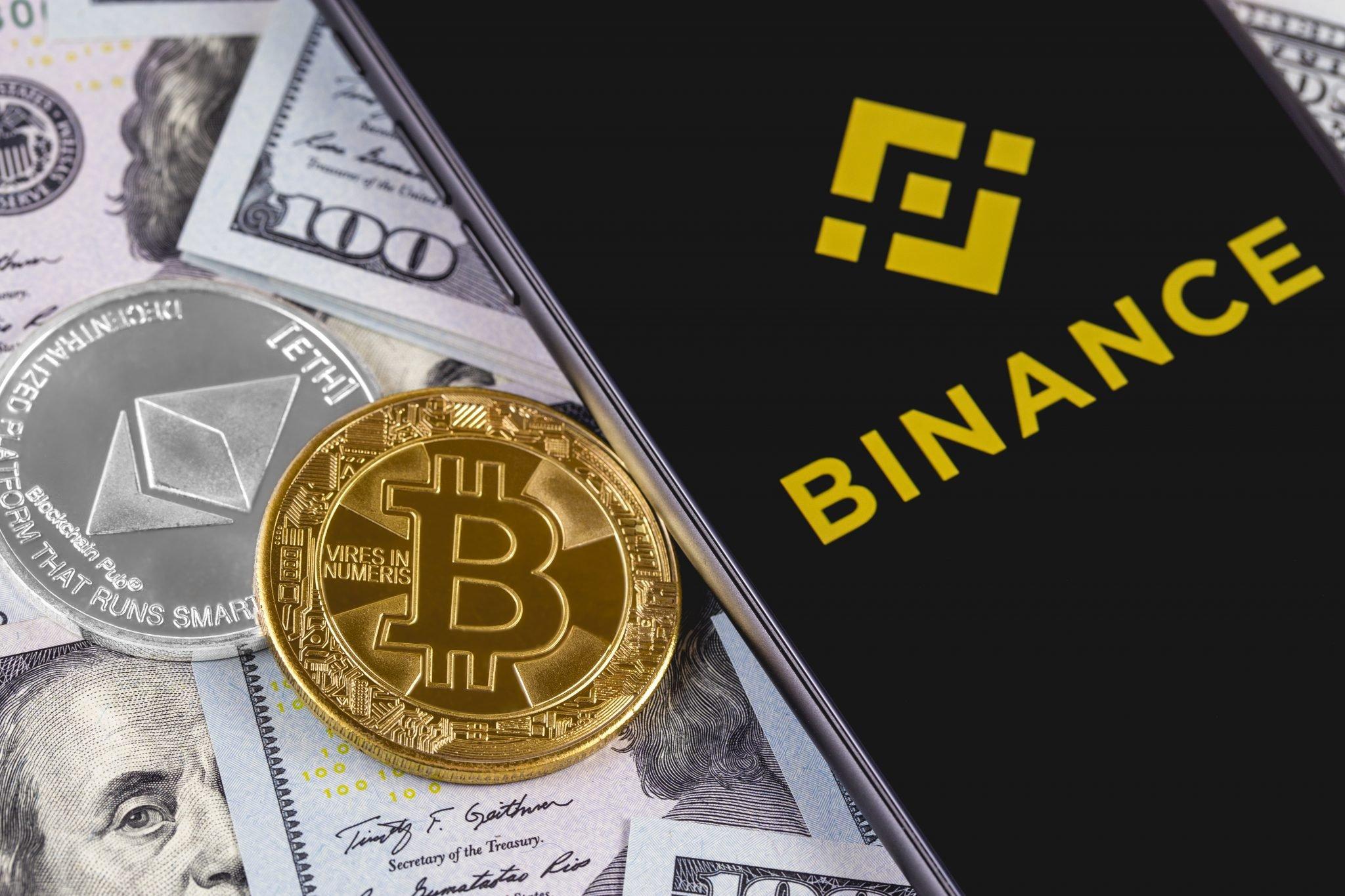 Apple iPhone and Binance logo and bitcoin, ethereum and dollars. Binance is a cryptocurrency exchange. Ekaterinburg, Russia - September 19, 2018
