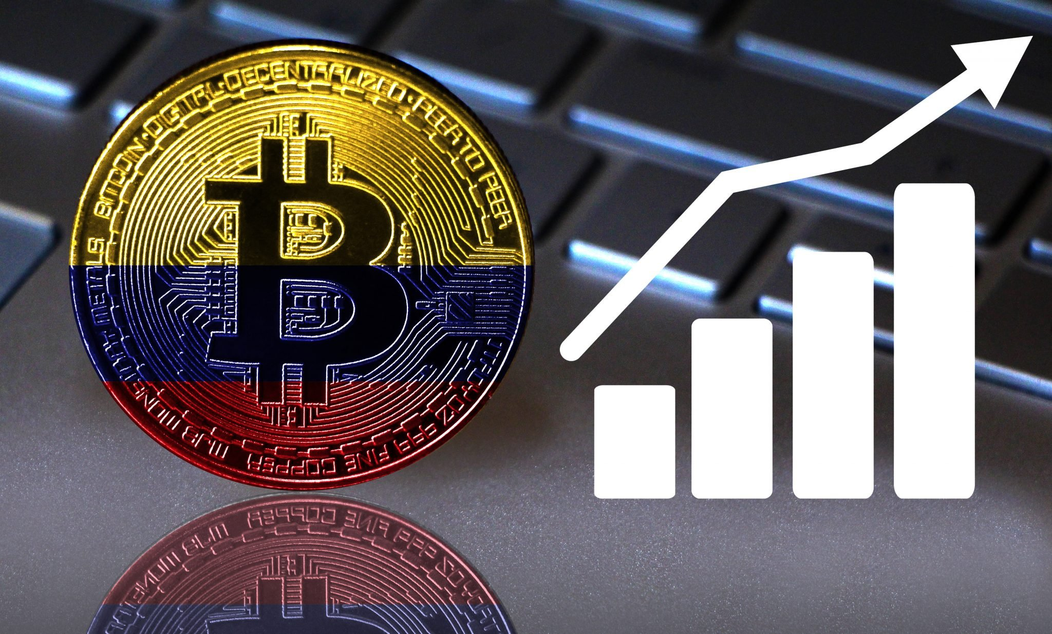 Bitcoin close-up on the keyboard background, the Colombia flag is shown on the bitcoin. Also the growth chart is shown.