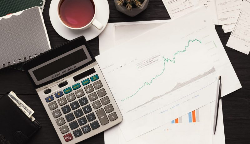 Calculator and business charts on workplace