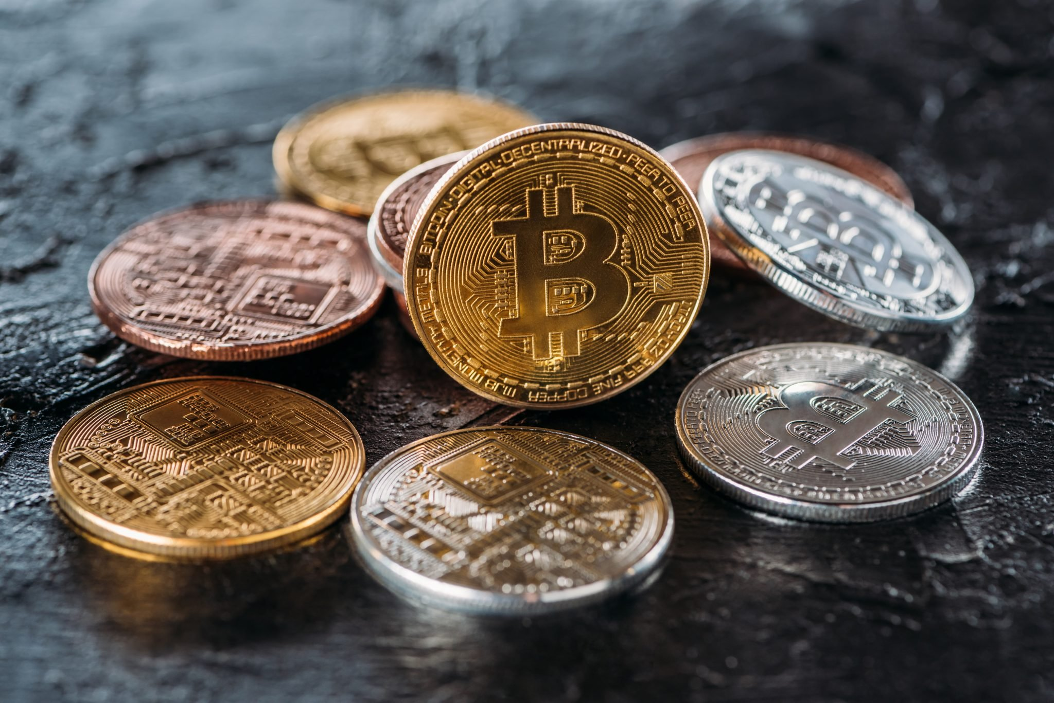close up view of various bitcoins on dark surface