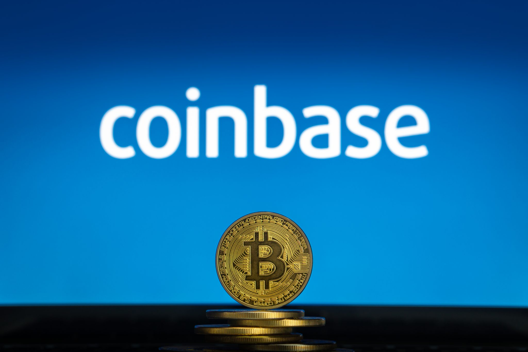 Coinbase logo on a computer screen with a stack of Bitcoin cryptocurency coins.