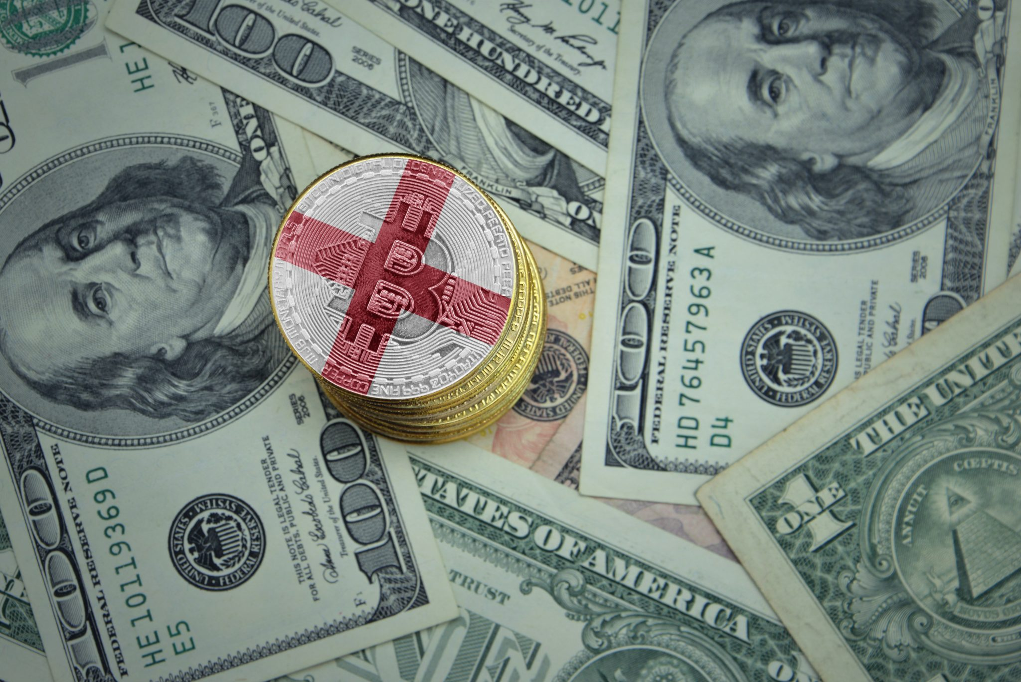 golden shining bitcoins with flag of england on a dollar money background. bitcoin mining concept.