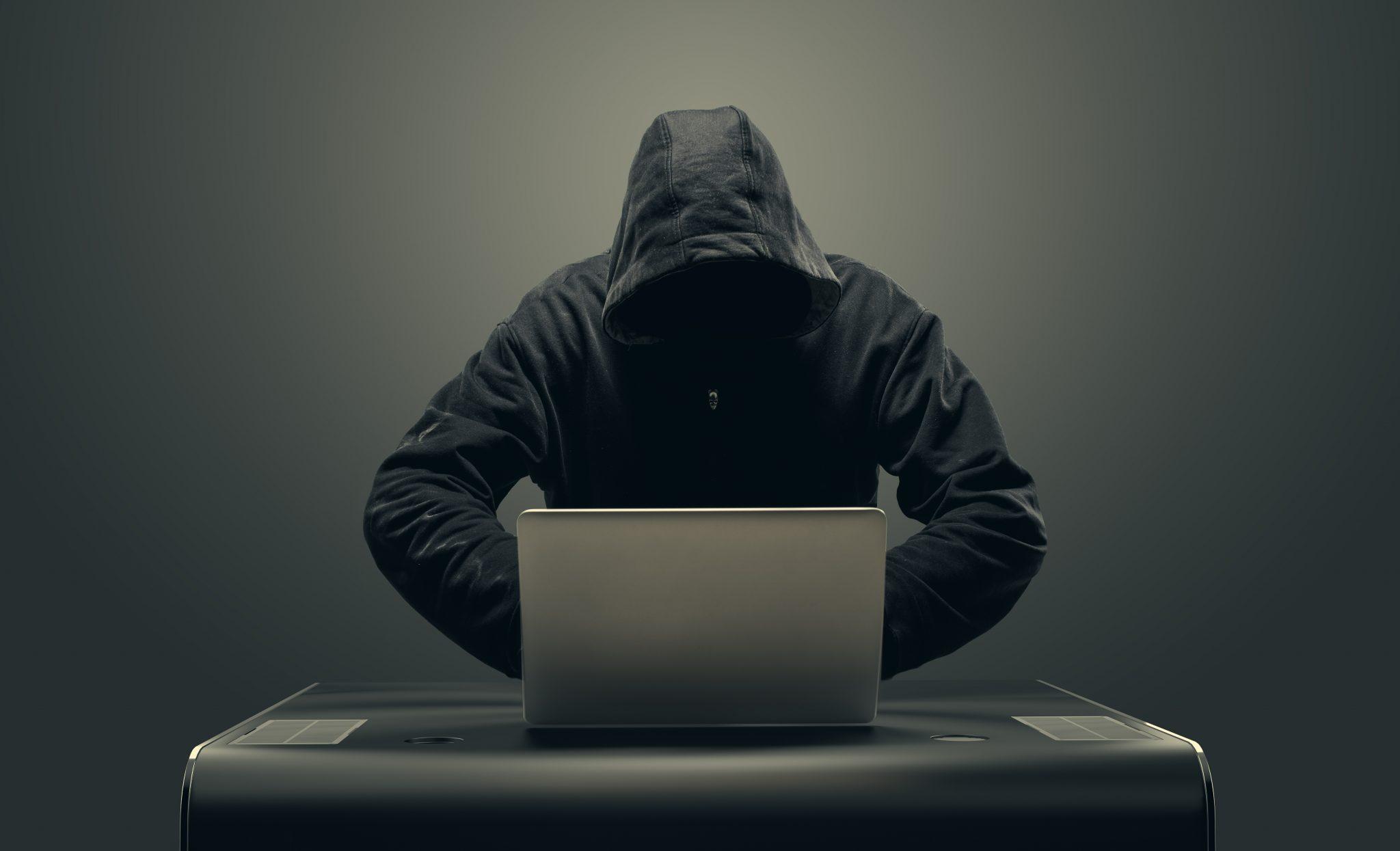 Hacker in mask by laptop