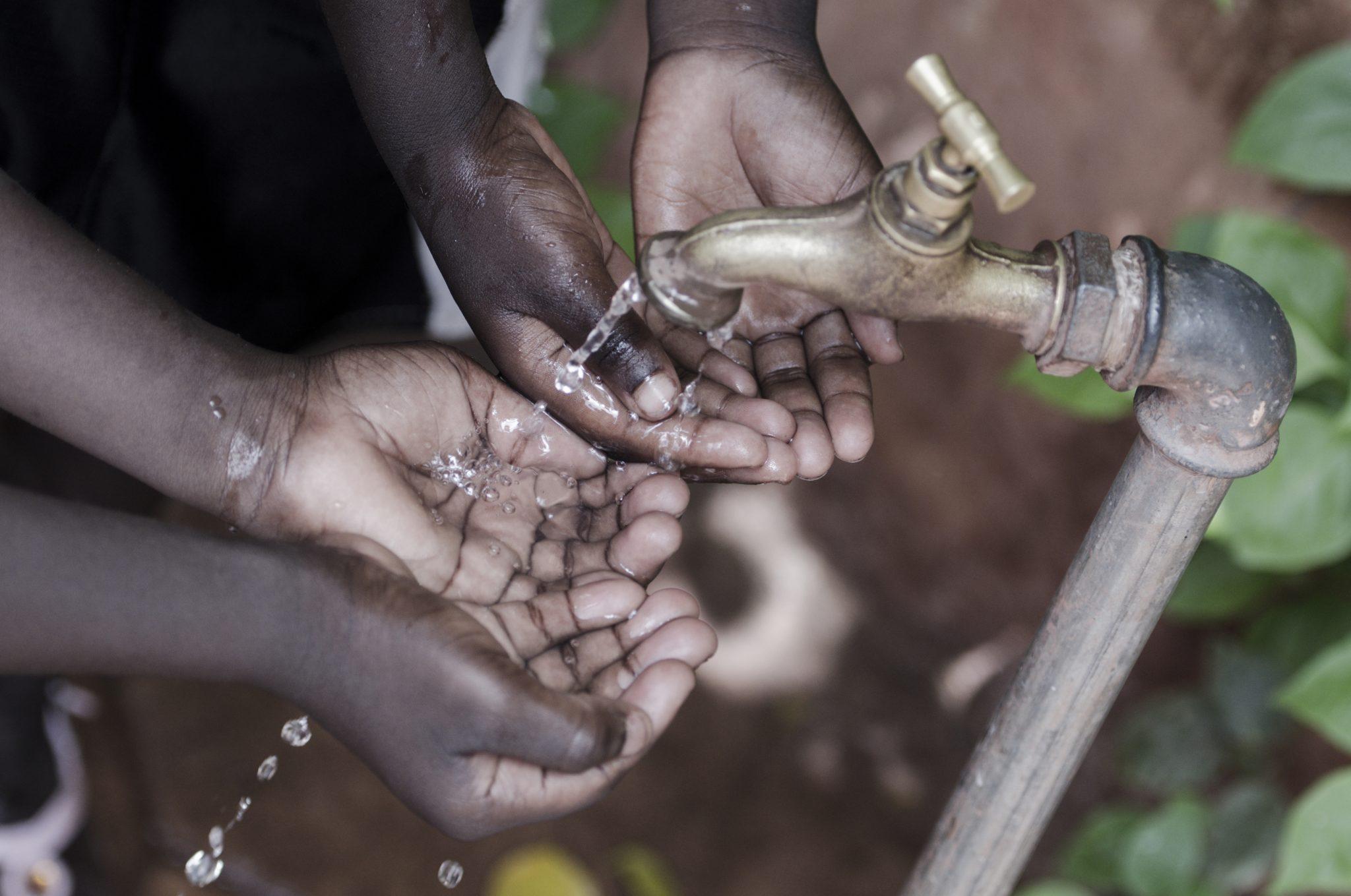 Hands of african children under tap