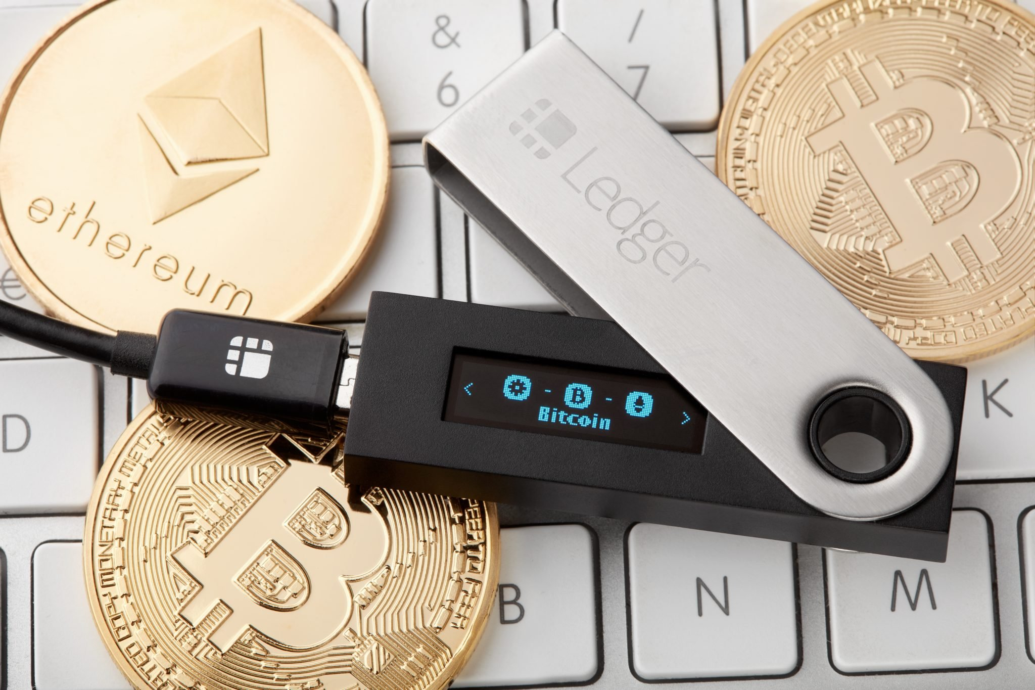 Ledger hardware wallet for cryptocurrency with golden bitcoin and ethereum