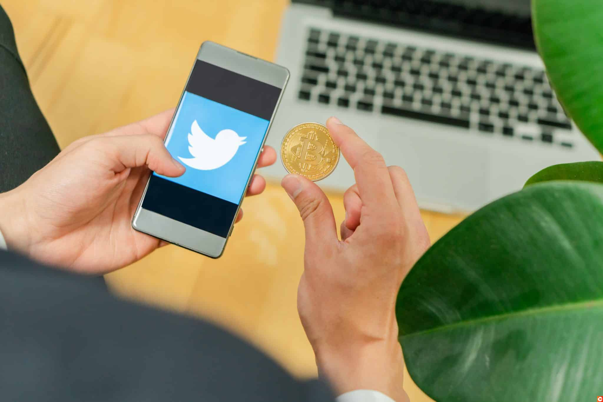 Ljubljana, Slovenia 29.4.2019: Businessman holding mobile smartphone with opened twitter logo and Bitcoin coin on a office desk