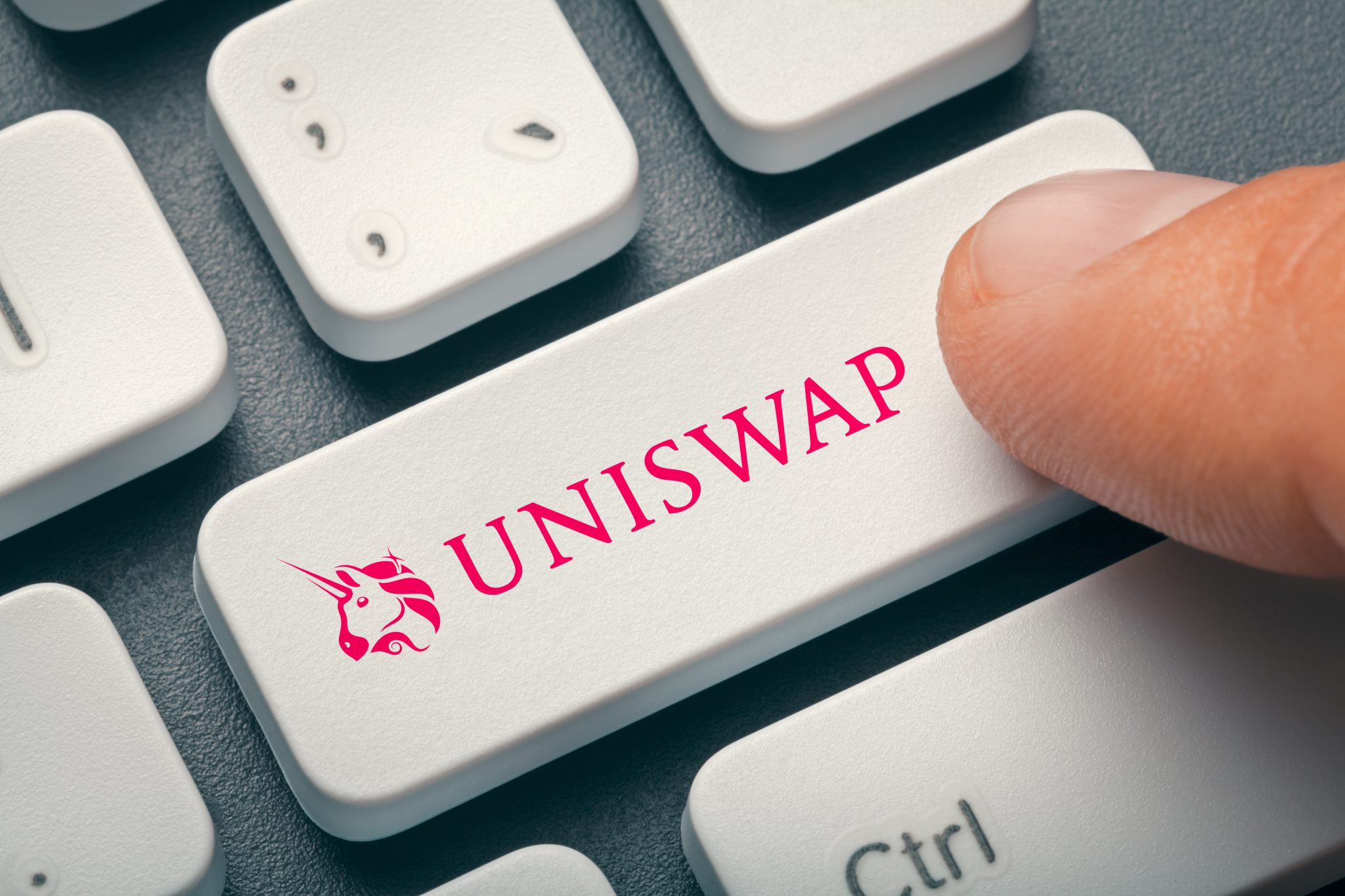 Male finger pressing computer key with uniswap   uni altcoin logo.  Cryptocurrrency mining or trading concept.