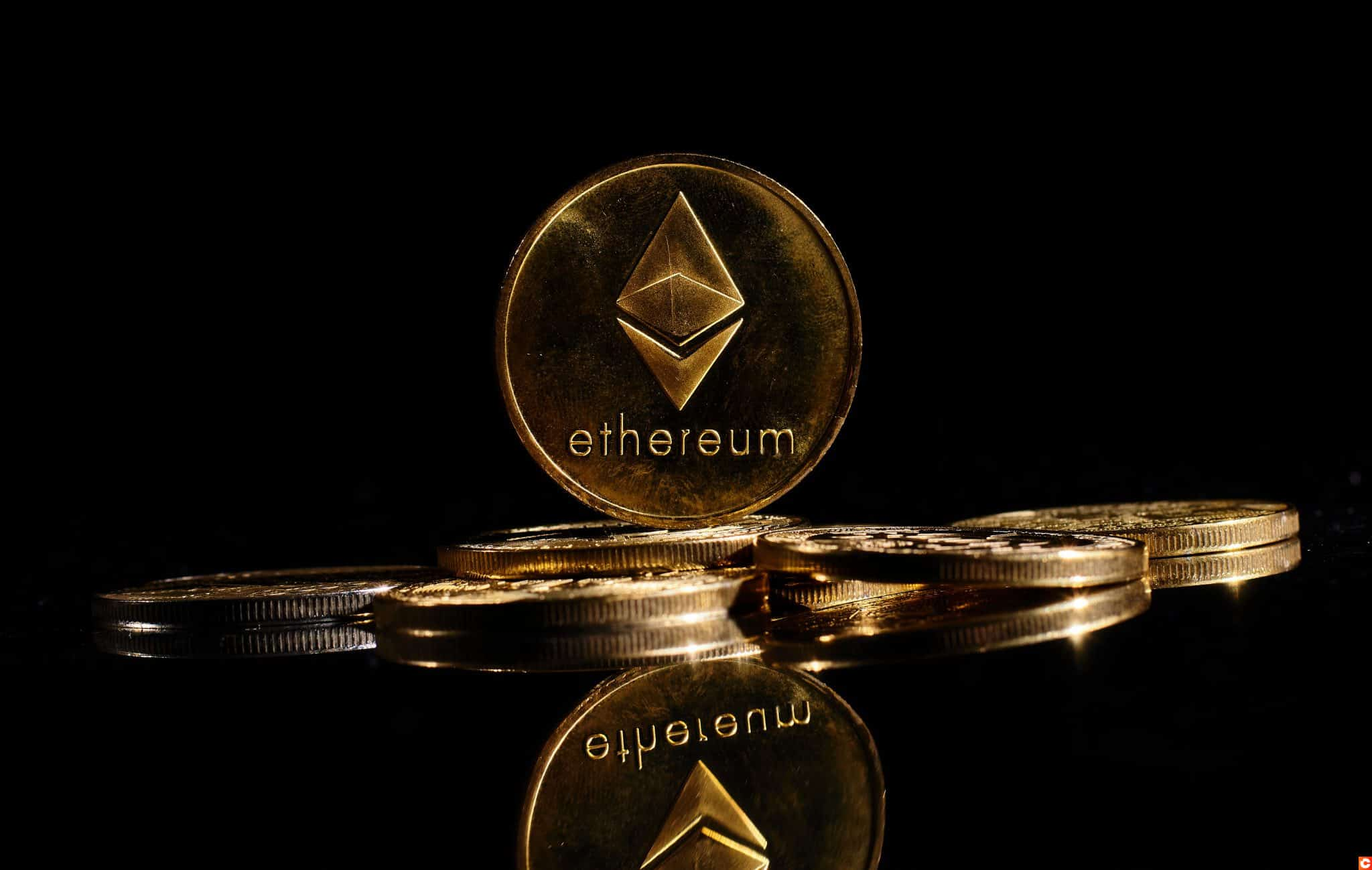 New cryptocurrency Ethereum ETH 2.0 on a top of bitcoin coins against black background. Closeup golden coin with Ether logo. A heap of decentralized digital currency. Crypto payment. Electronic money