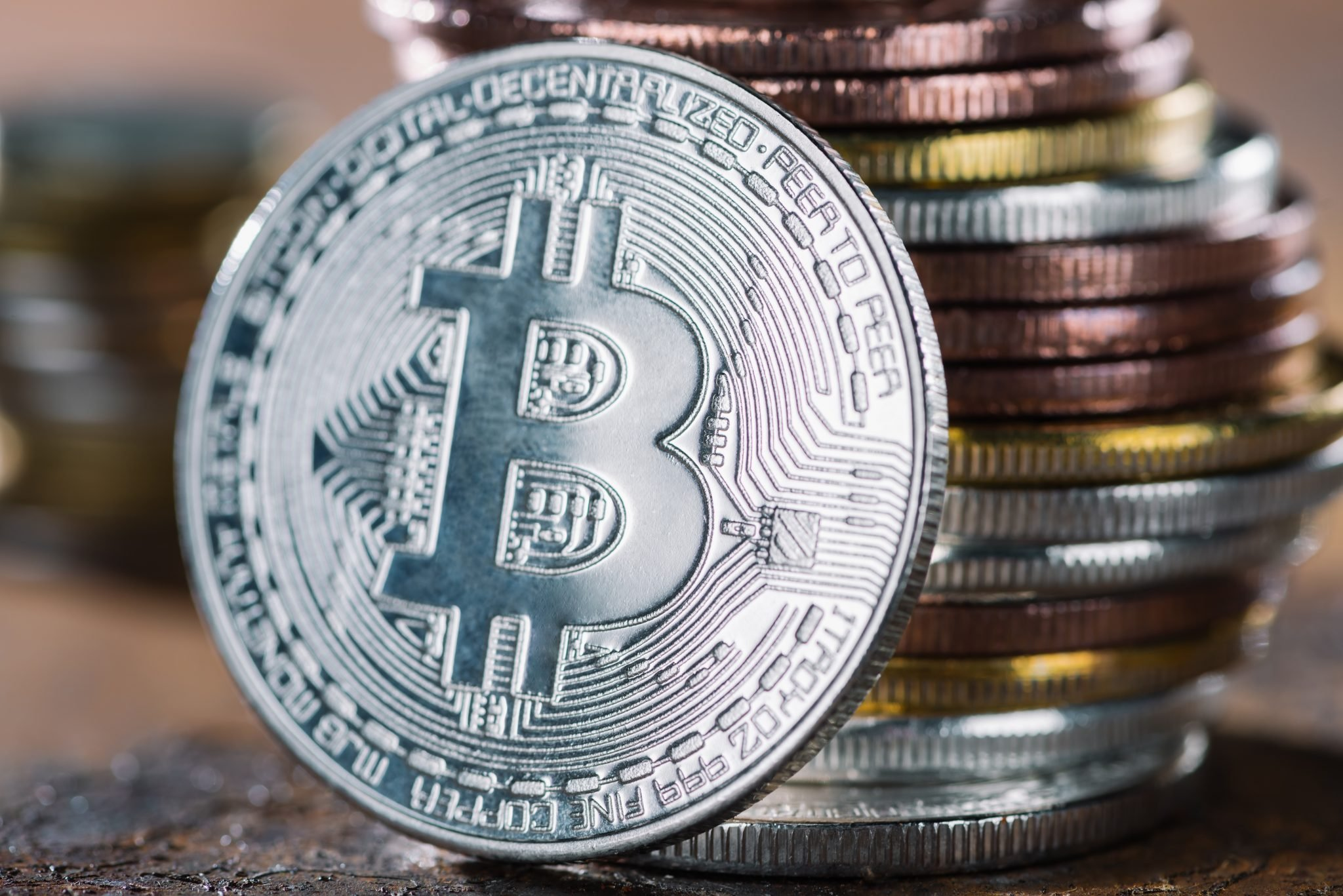 selective focus of silver bitcoin and pile of bitcoins behind