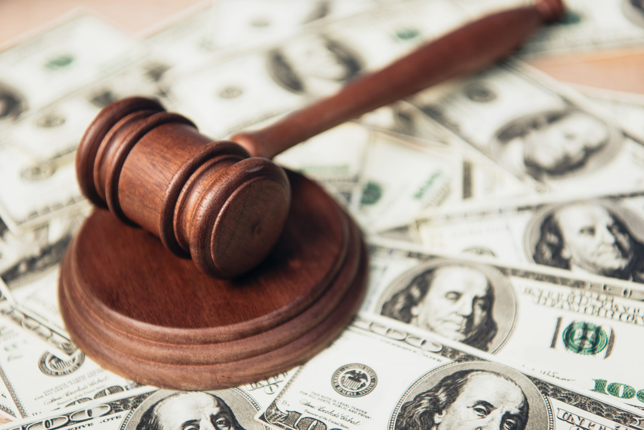 selective focus of wooden gavel near dollar banknotes