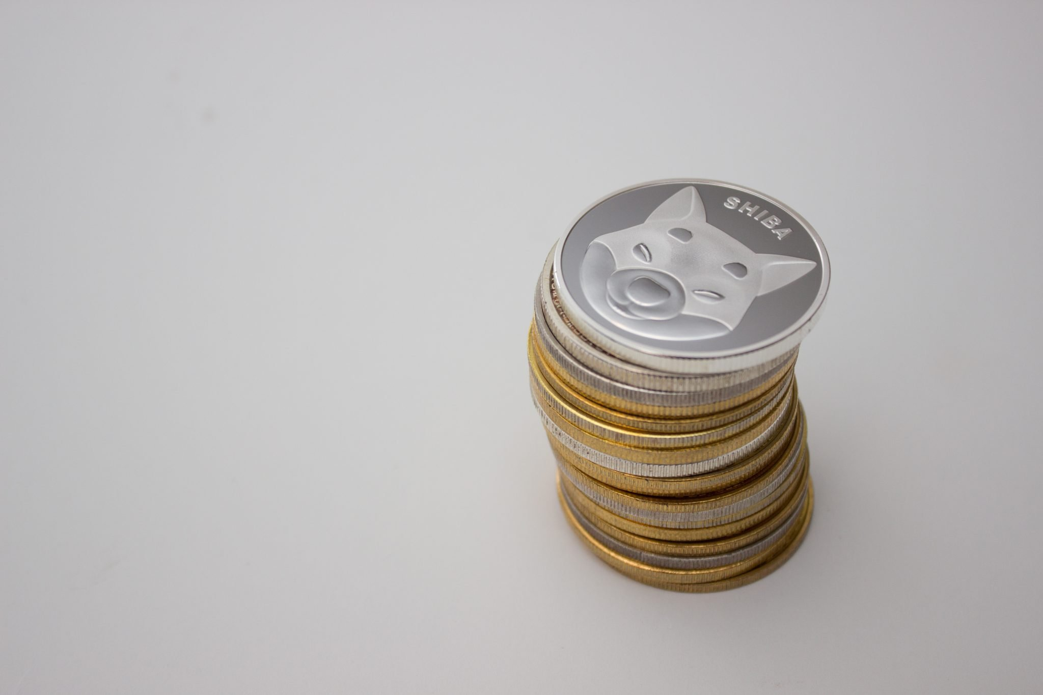 Stack of shiba INU coins over white background