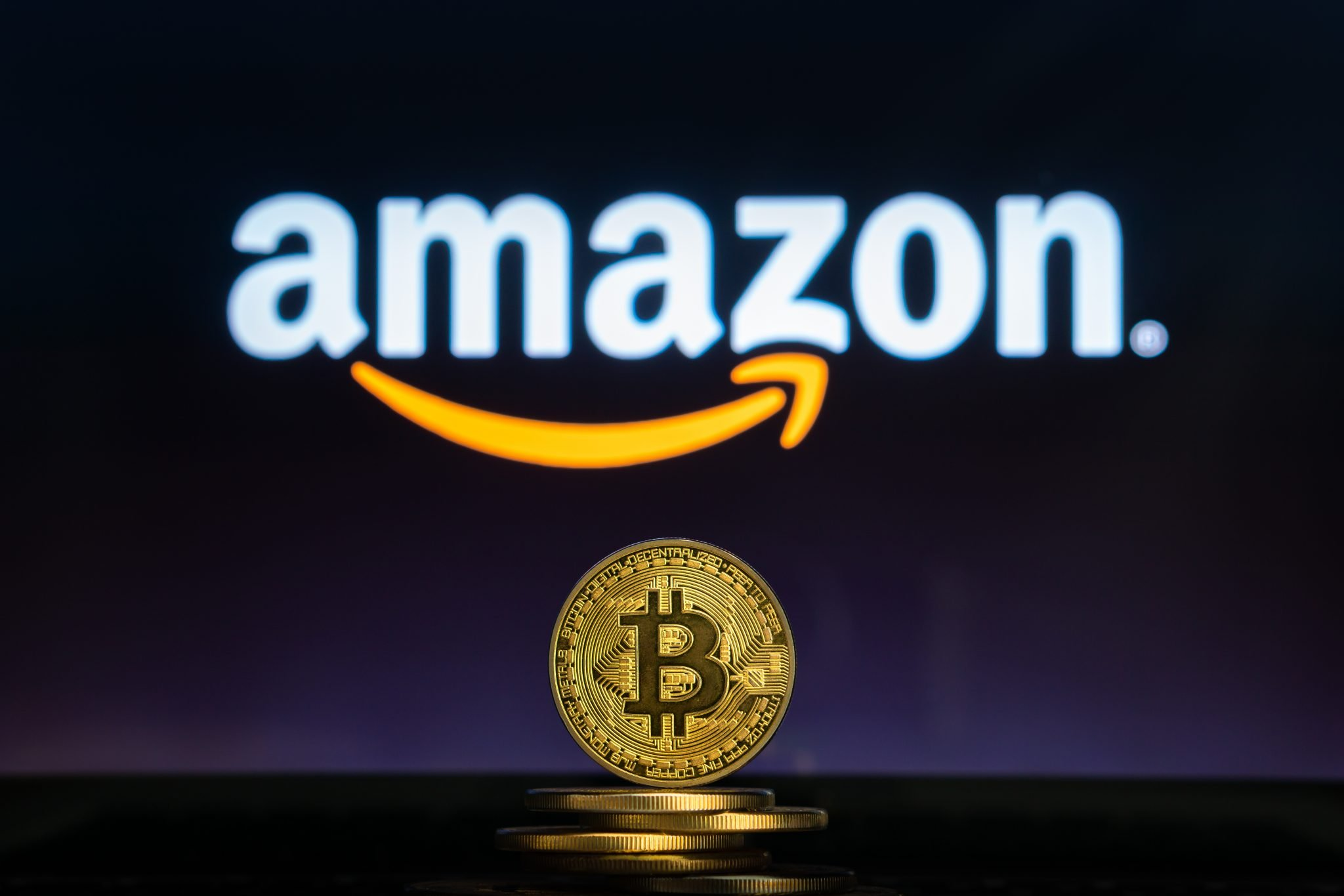Amazon logo on a computer screen with a stack of Bitcoin cryptocurency coins.