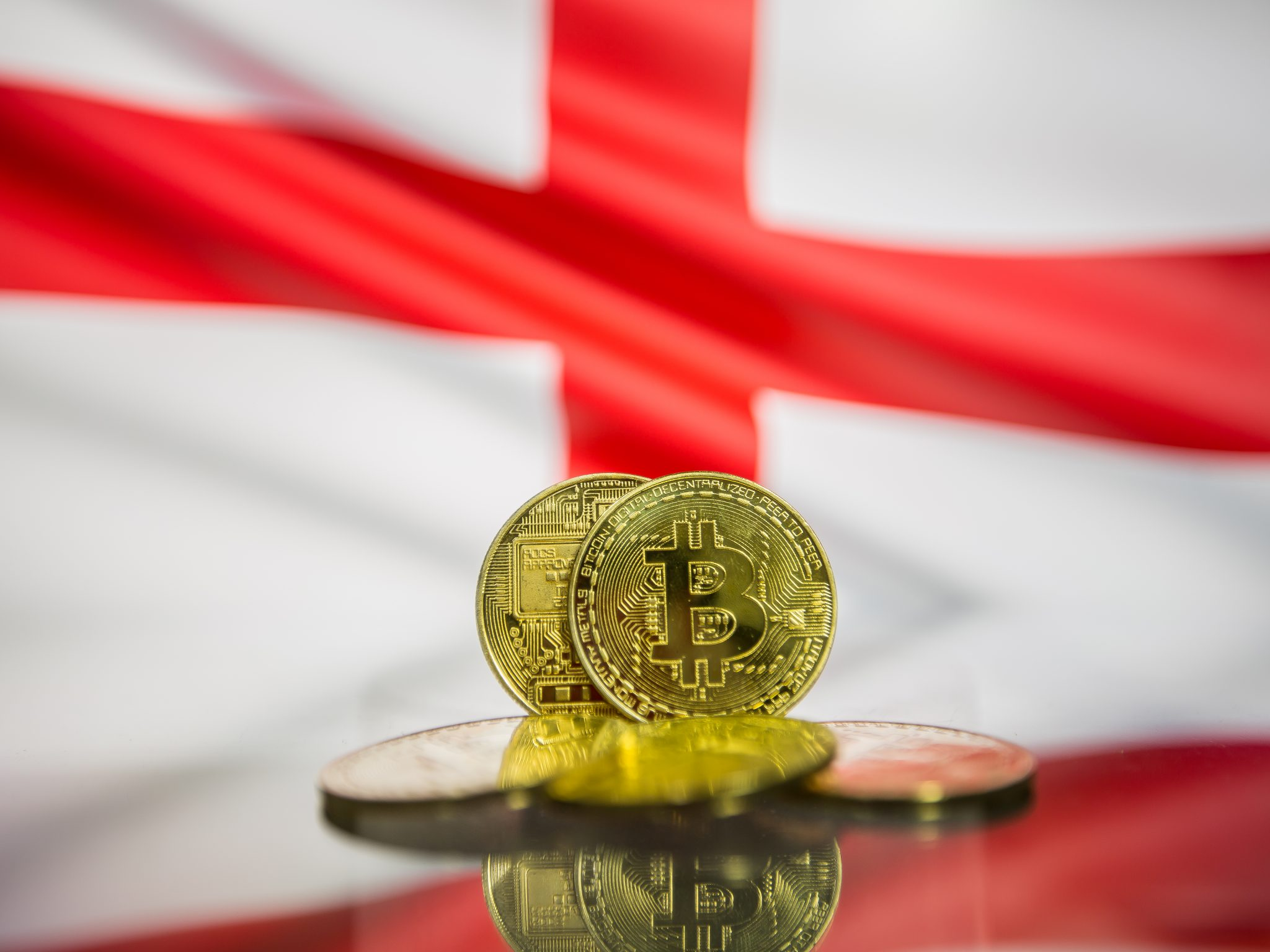 Bitcoin gold coin and defocused flag of England background. Virtual cryptocurrency concept.