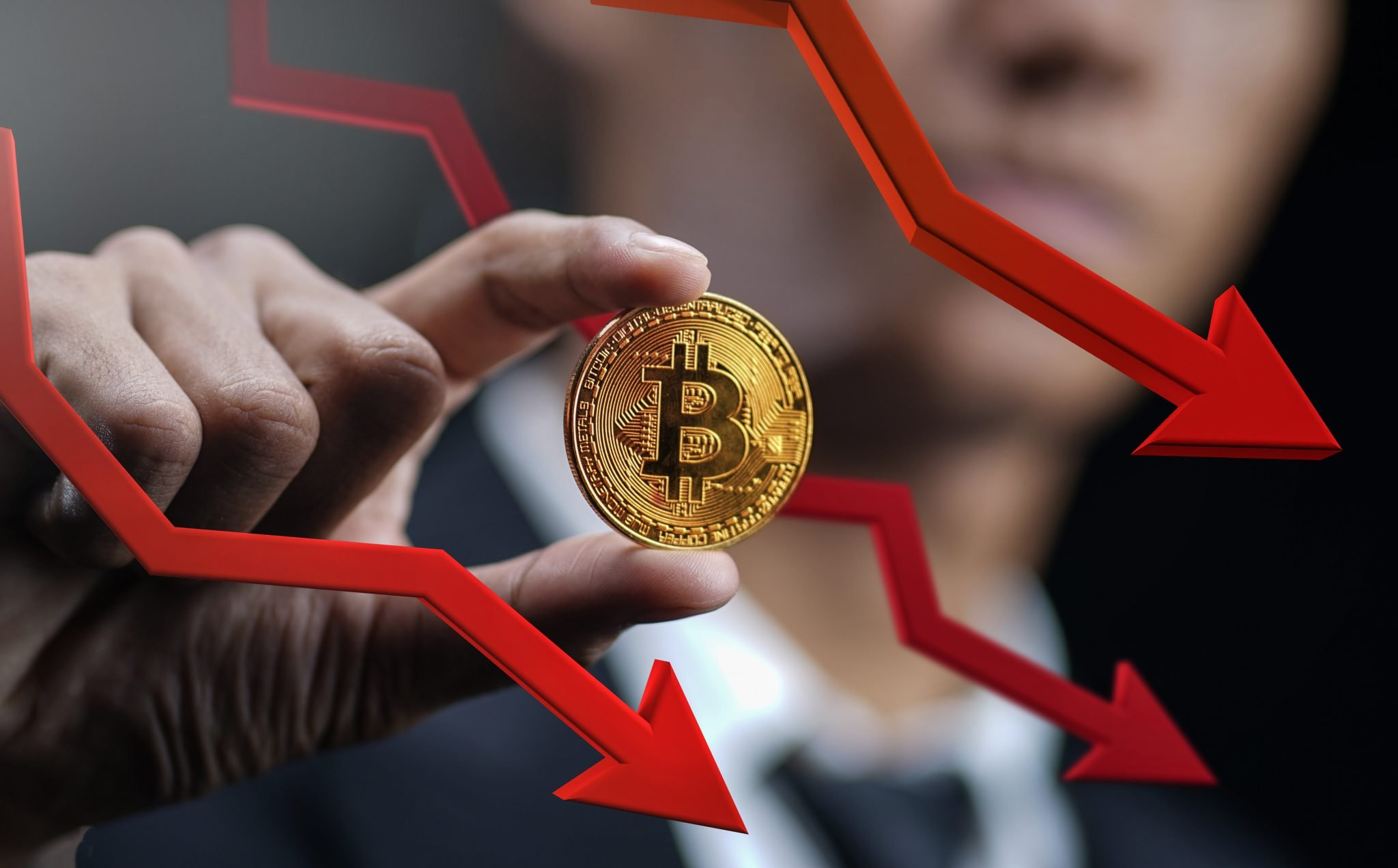 Bitcoin Price Falling Down. Businessman Holding Bitcoin With Red 3D Arrow Down