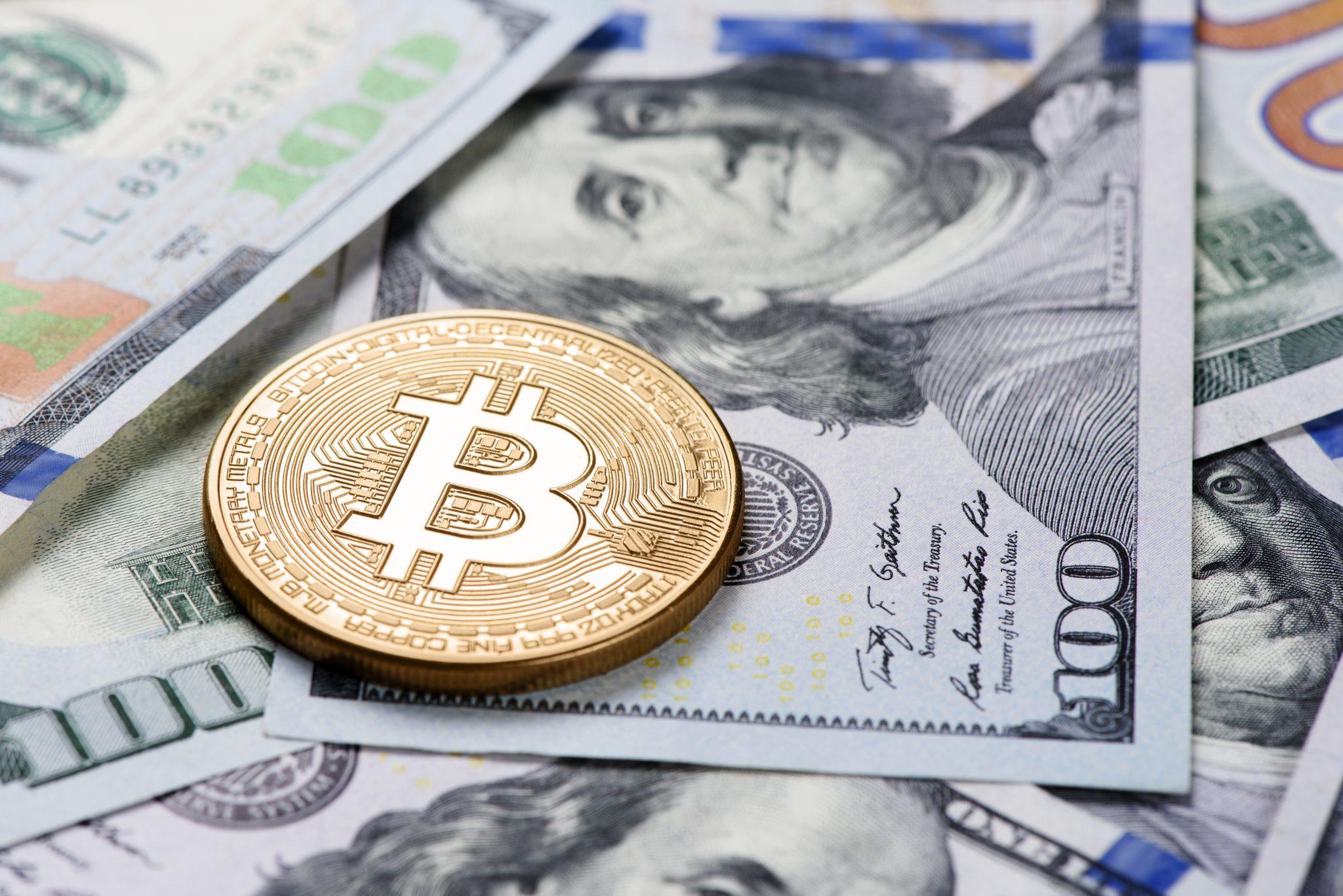 Golden Bitcoin coin on a us dollars
