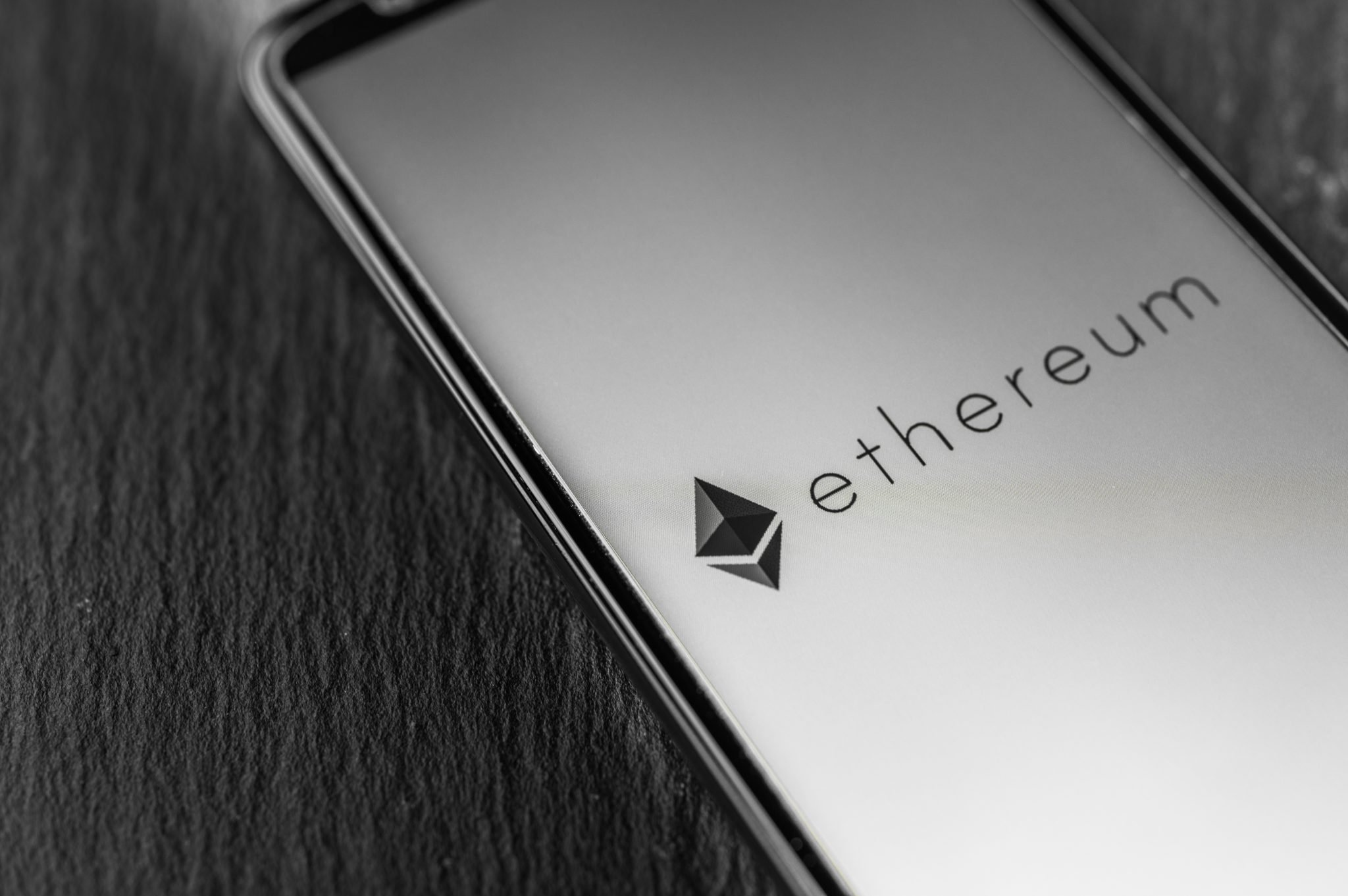 Logo of Ethereum blockchain money cryptocurrency on screen of smartphone.
