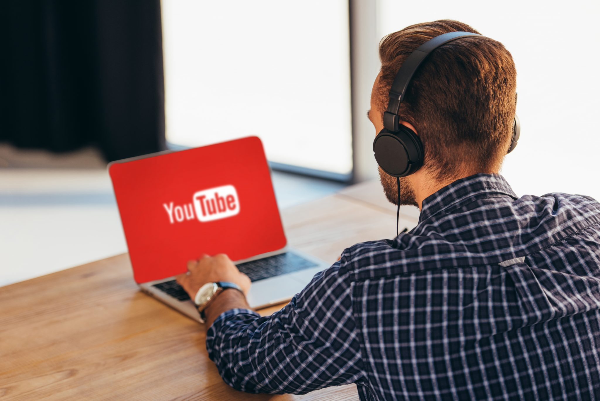 partial view of man in headphones using laptop with youtube logo on screen in office