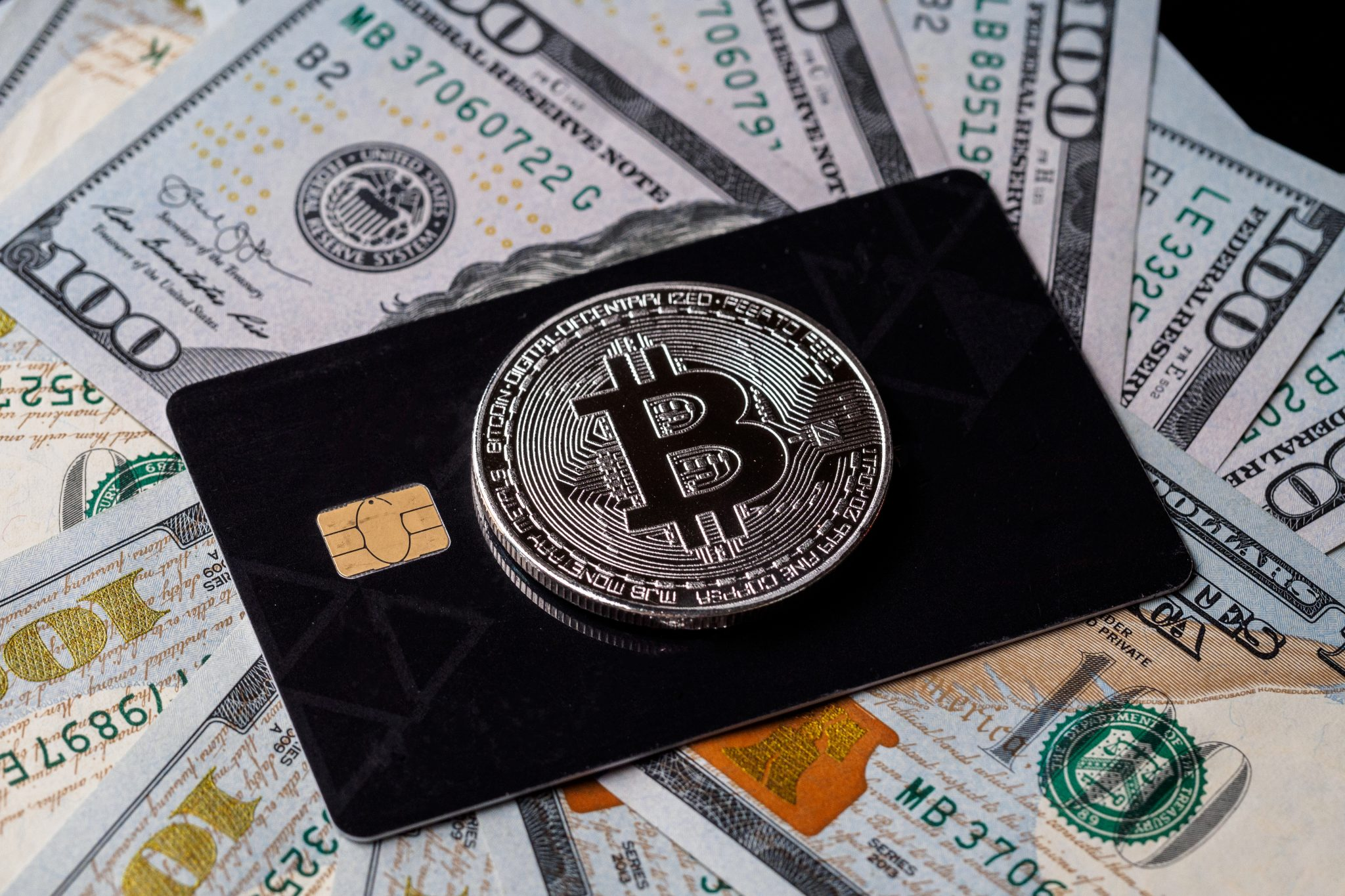 Silver bitcoin with credit card on top of dollars banknote backg