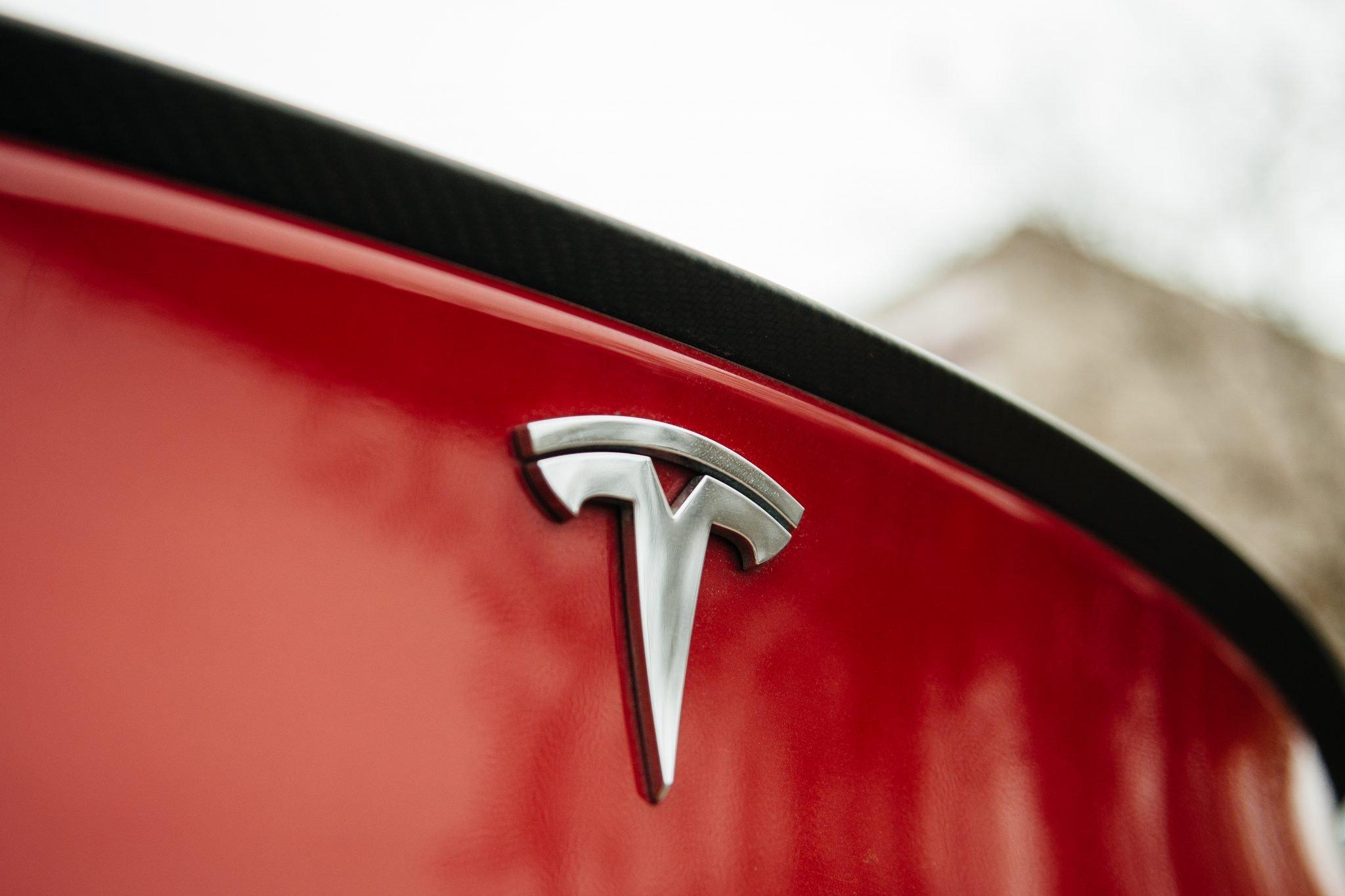 Tesla Motors logo on a red car.