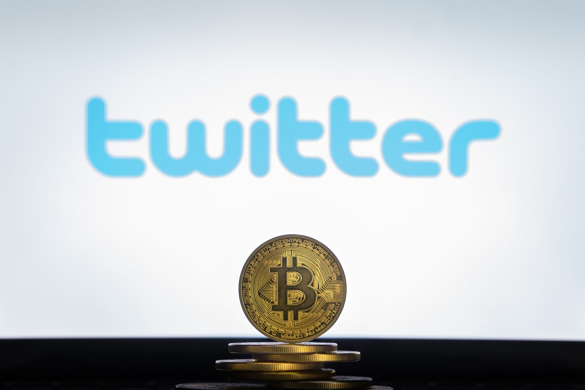 Twitter logo on a computer screen with a stack of Bitcoin cryptocurency coins.