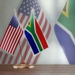 American and South African flag pair on desk over defocused background. Horizontal composition with copy space and selective focus.