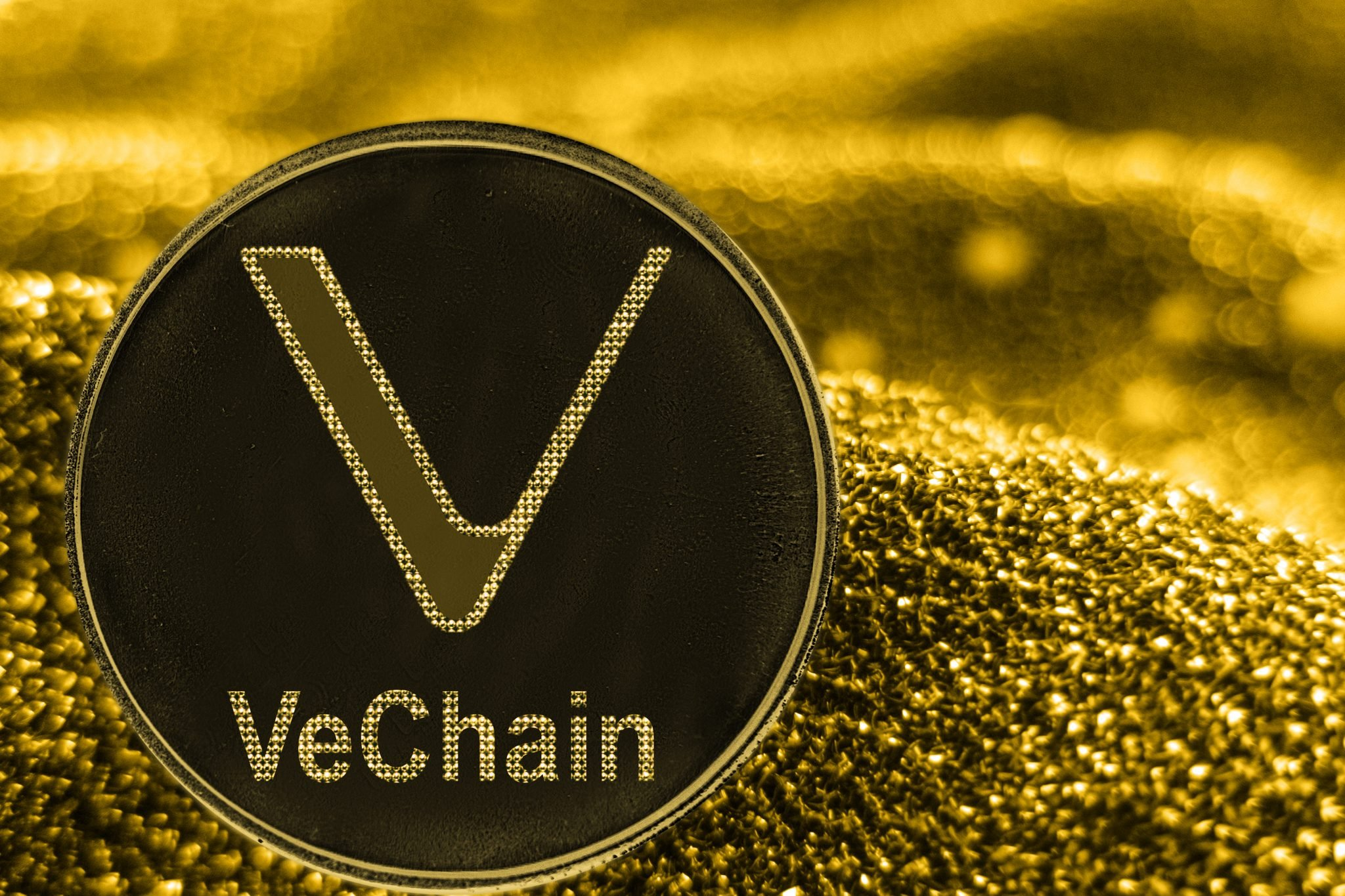 Coin cryptocurrency VeChain VET on golden background.