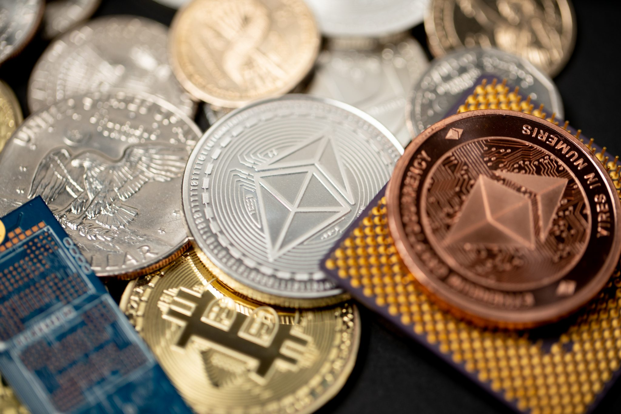 Ethereum coin in gold and copper, next to microchip and us one dollar coin. Concept of crypto mining, computing power and cost of mining crypto currencies