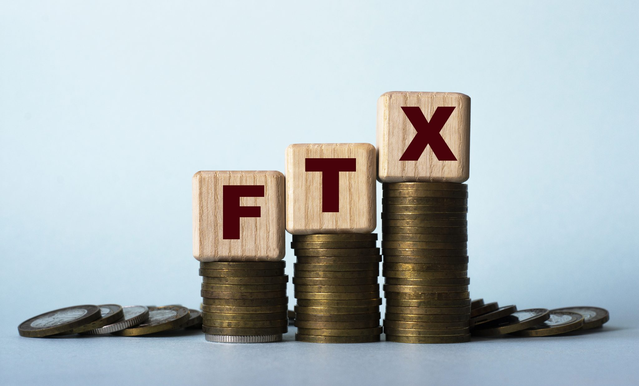 FTX - acronym on wooden cubes. Which stand on stacks of coins on a light background. Business concept