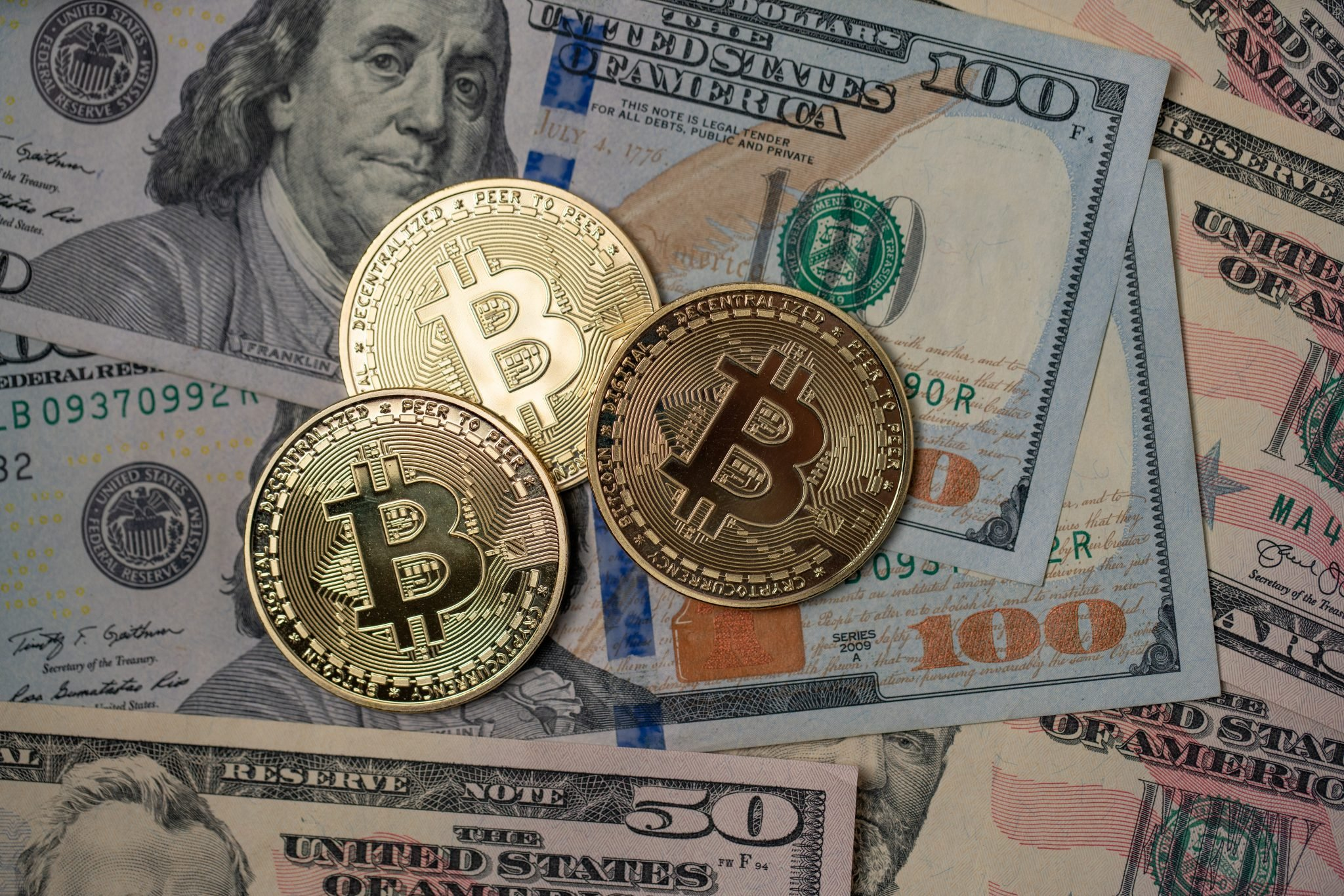 Gold Bitcoin coins on top of 100 Dollar Banknotes. Crypto currency and Fiat currency. Digital Money concept. Trading Crypto and Dollar