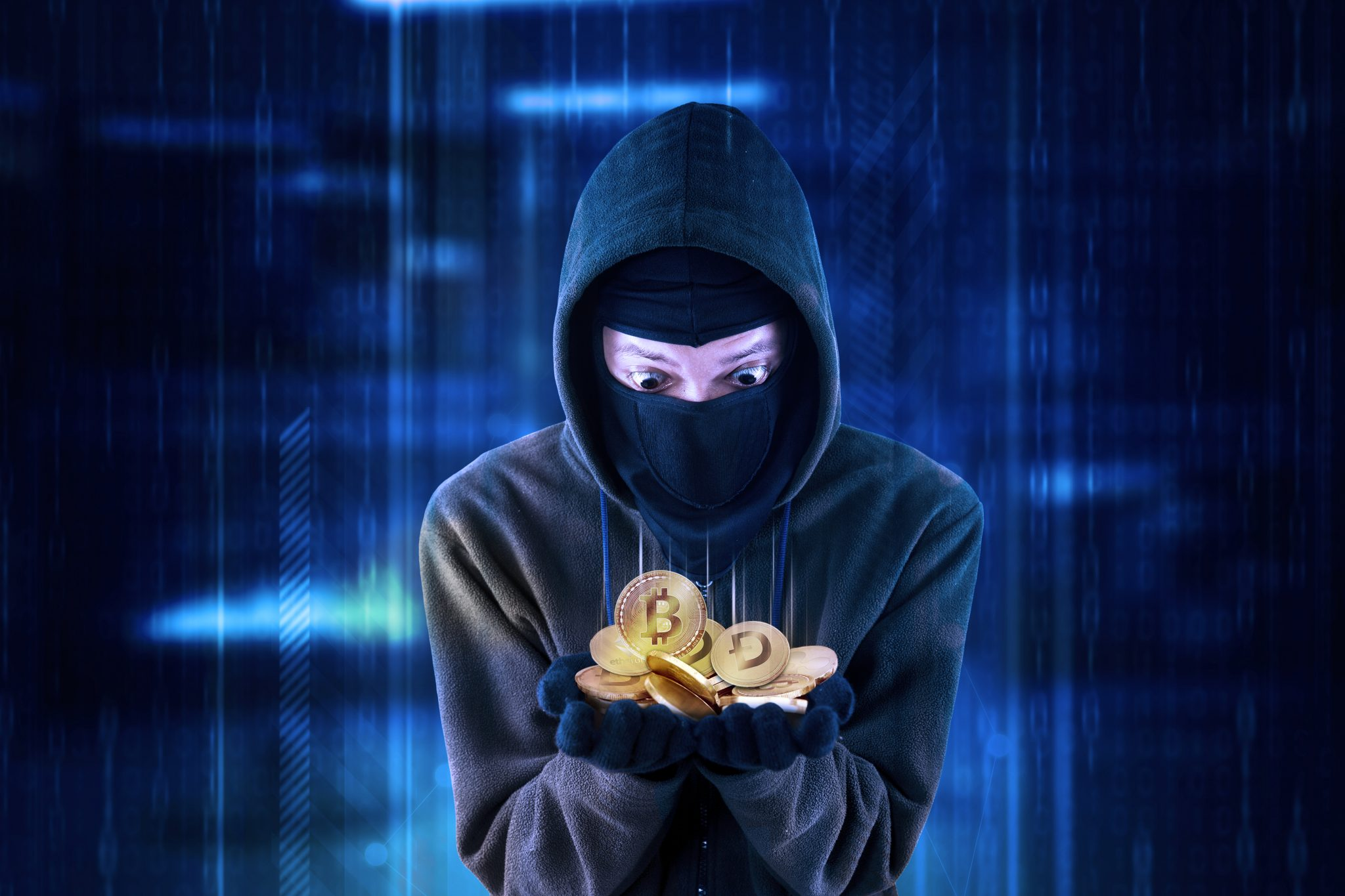 Hooded hacker looks shocked while getting cryptocurrency coins and standing with virtual screen background