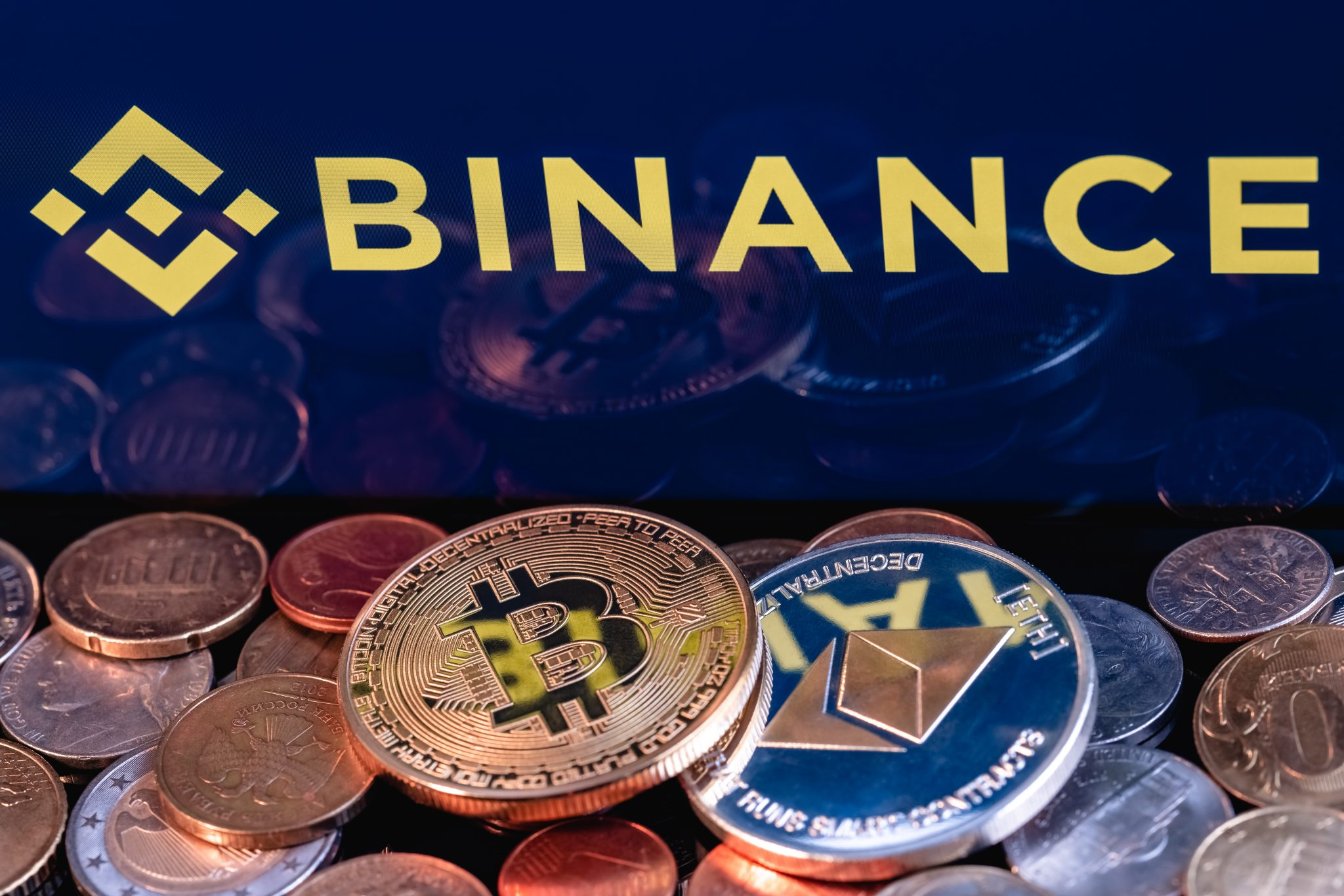 Kazan, Russia - May 17, 2021: Binance is cryptocurrency exchange that provides a platform for trading various cryptocurrencies. Ethereum coin and Bitcoin on the background of the BINANCE inscription.
