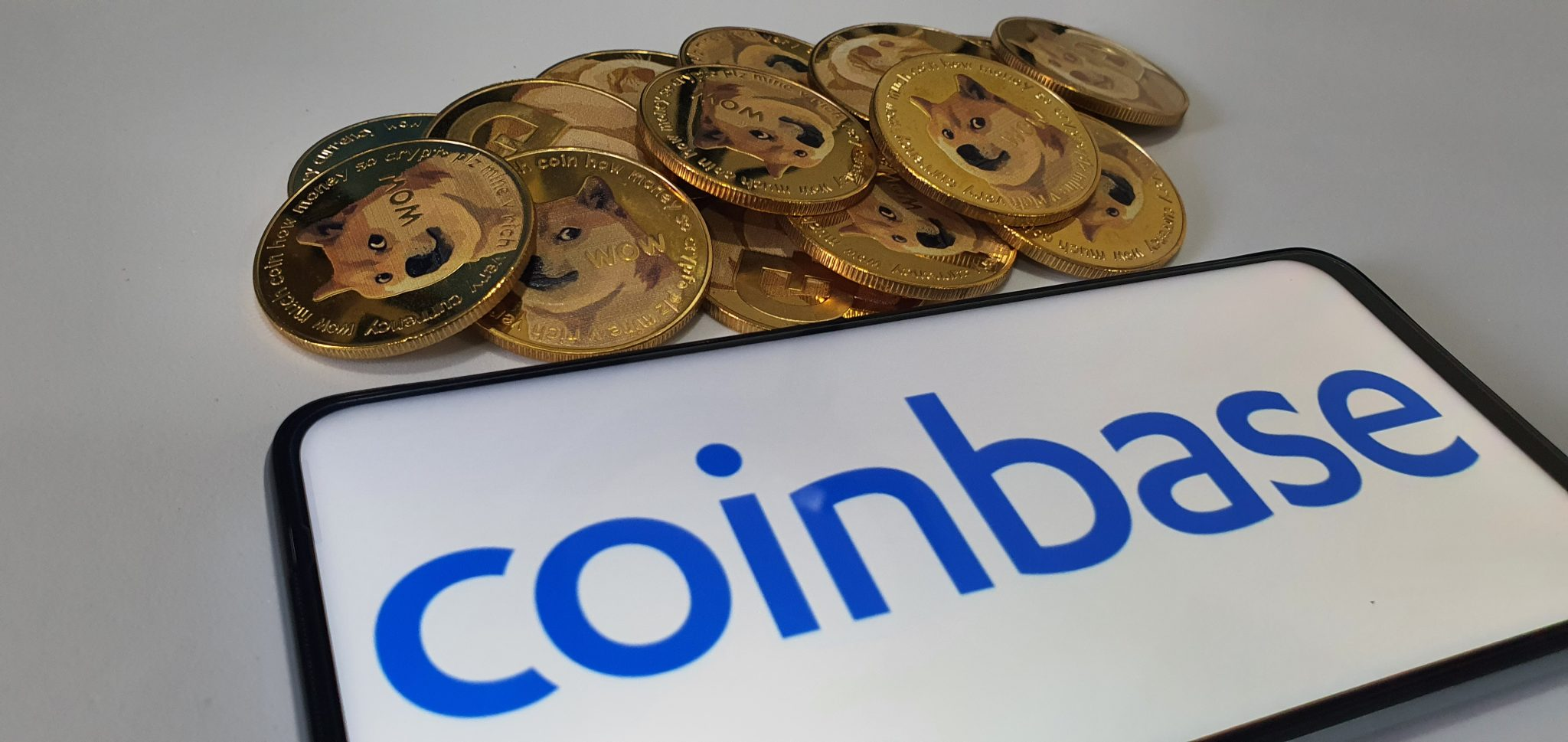 Kuching, Sarawak Malaysia - June 2, 2021: Macro view of gold color shiny coins with Dogecoin symbol and Coinbase background