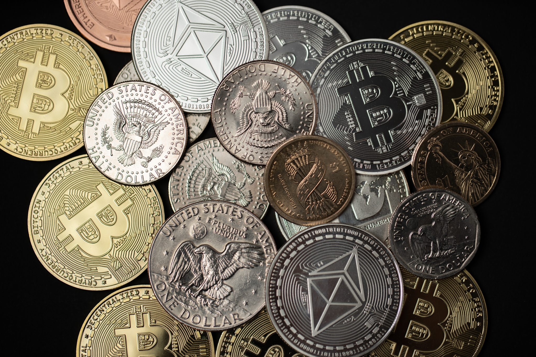 One dollar coin on half dollar and gold Bitcoin coins. Digital crypto currency Bitcoin, Ethereum and Litecoin with USD