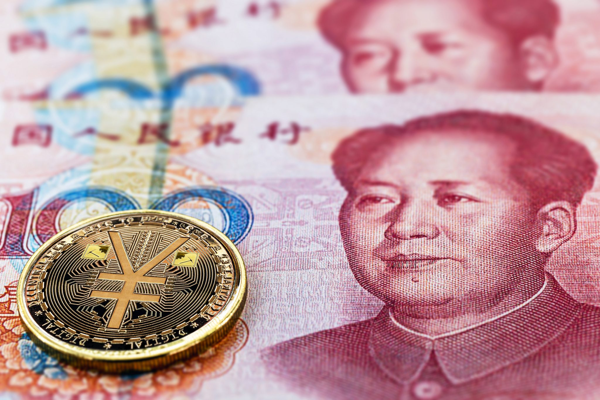 one hundred yuan banknotes, next to an e-RMB gold coin, digital version of the yuan. Concept of new digital currency of the popular republic of china