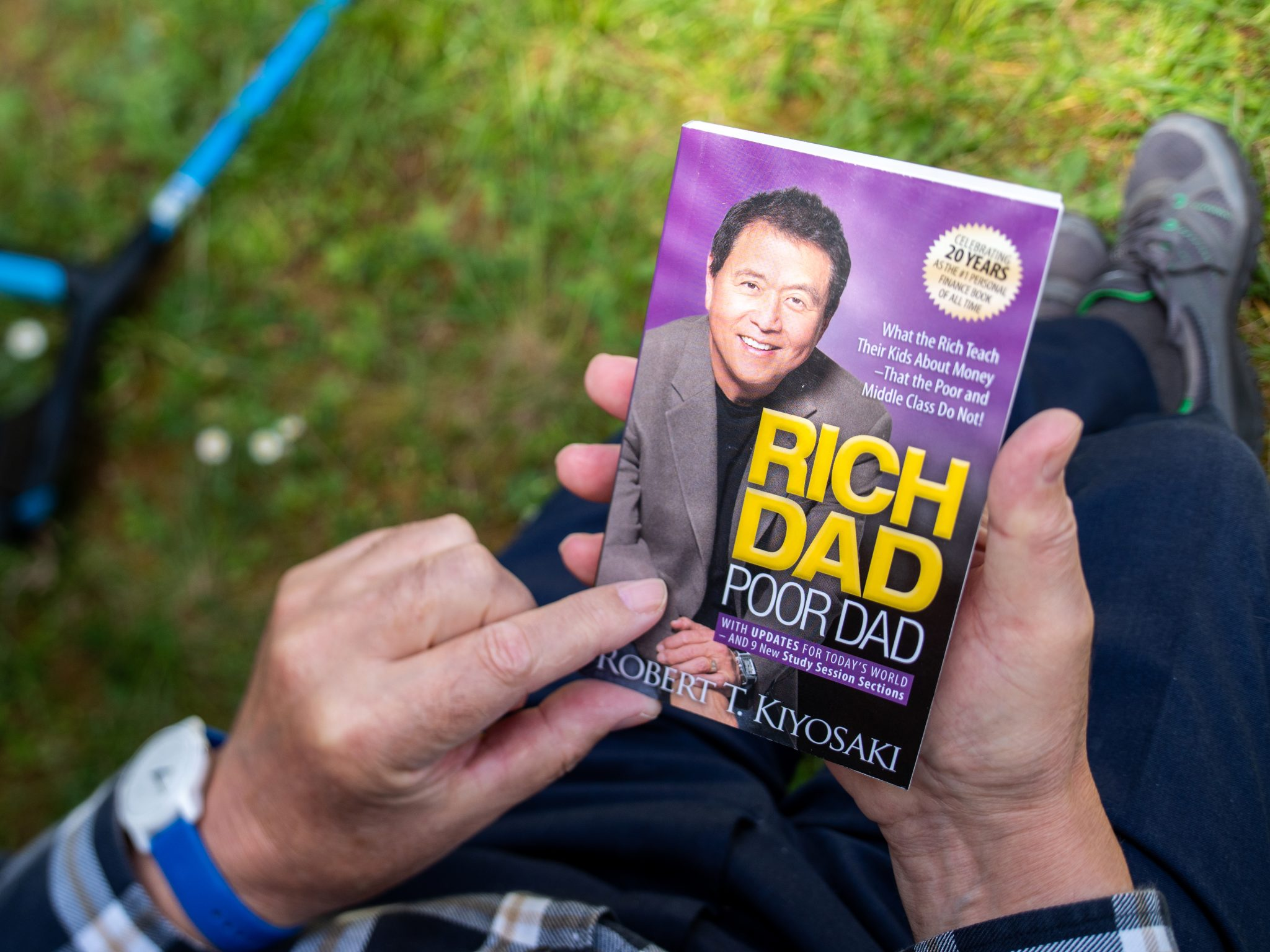 Overhead POV view of senior male hand hodling in had reading the iconic book Rich dad and Poor Dad